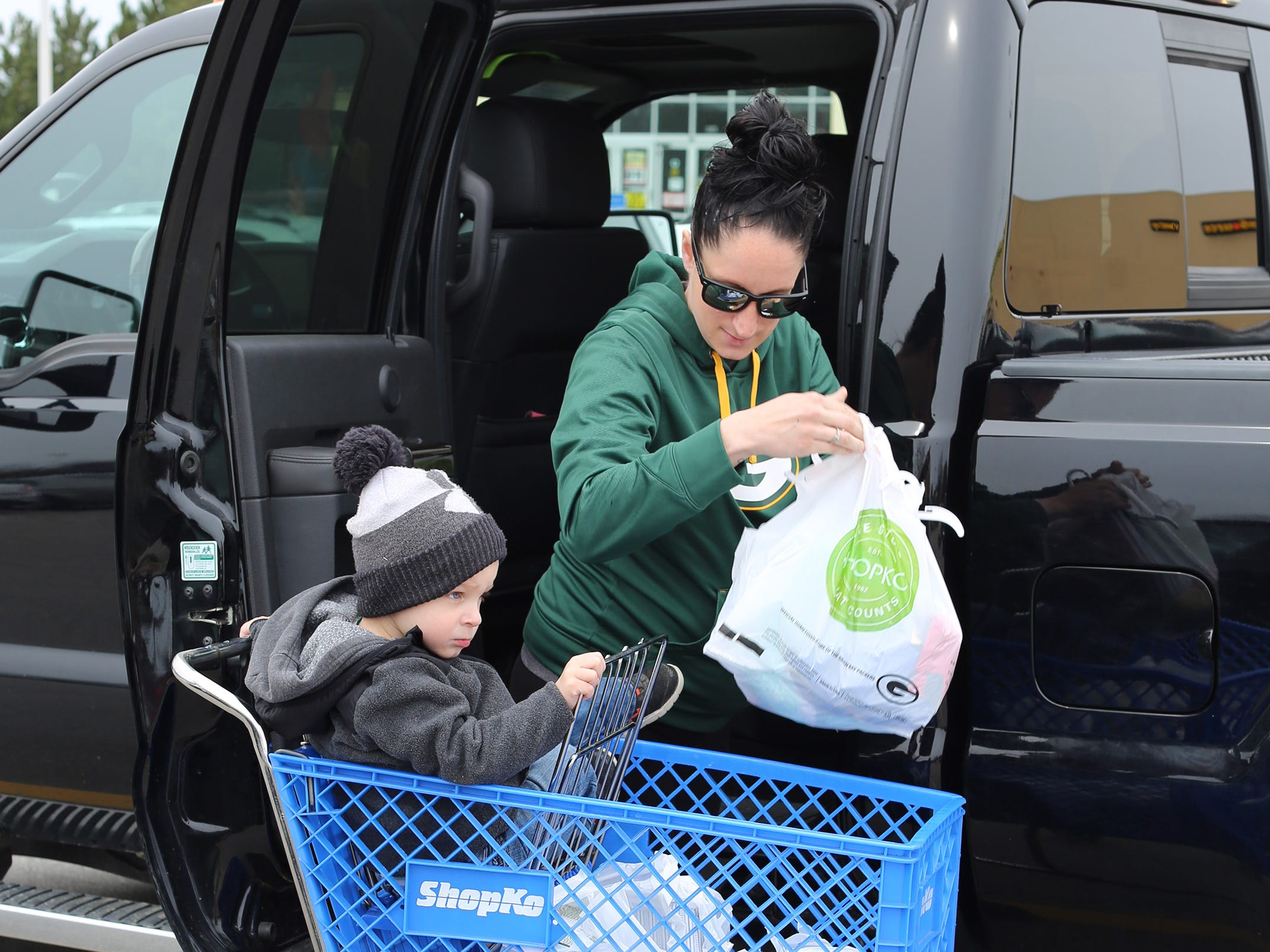 """Samantha Jones of Sheboygan Falls, Wis. takes bags of clothes she bought at ShopKo, Saturday, May 11, 2019, in Sheboygan, Wis. Jones, who was with her son Nicholas, 2, said, """"It is what it is. A lot of stores are closing."""""""