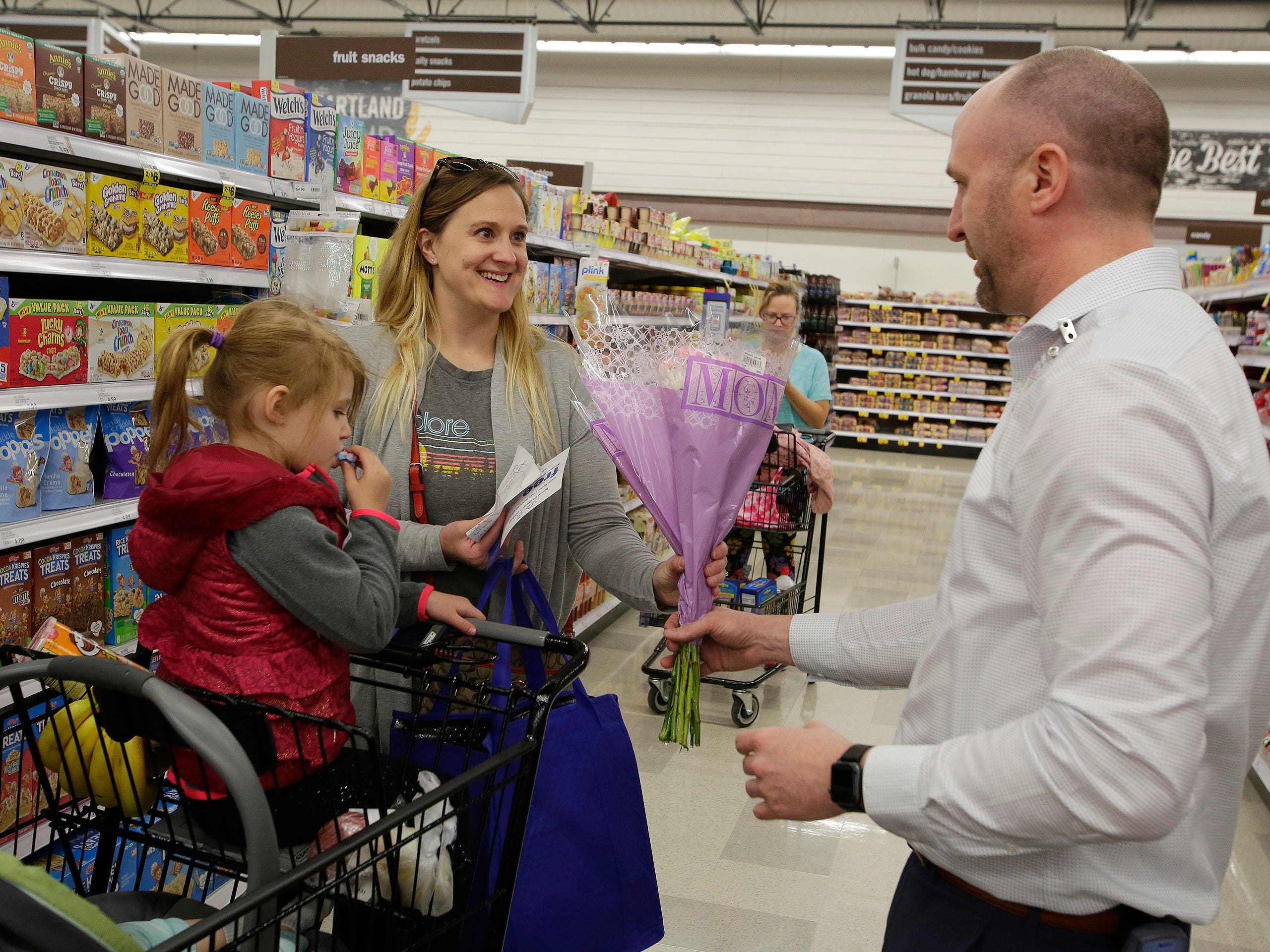 Shelly Nole of Sheboygan, center, is all smiles as she is presented gifts by Meijer Store Director Jeff  Kietzman at Meijer, Saturday, May 11, 2019, in Sheboygan, Wis. The store randomly handed out gifts to moms Saturday. Noles had her children Hannah 3, and Amelia, 11 months with her.