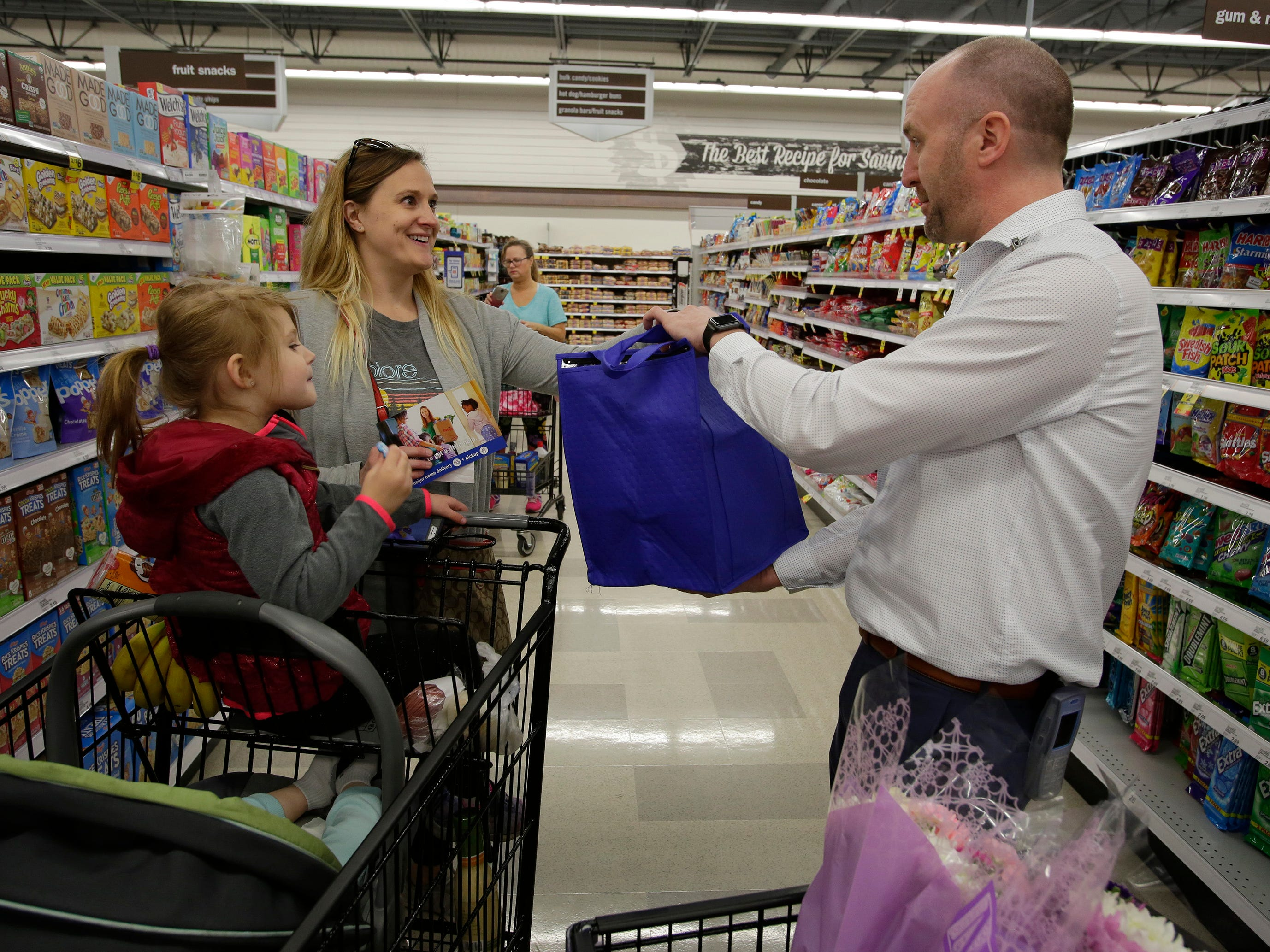 Shelly Nole of Sheboygan is all smiles as she is presented gifts by Meijer Store Director Jeff  Kietzman at Meijer, Saturday, May 11, 2019, in Sheboygan, Wis. The store randomly handed out gifts to moms Saturday. Noles had her children Hannah 3, and Amelia, 11 months with her.
