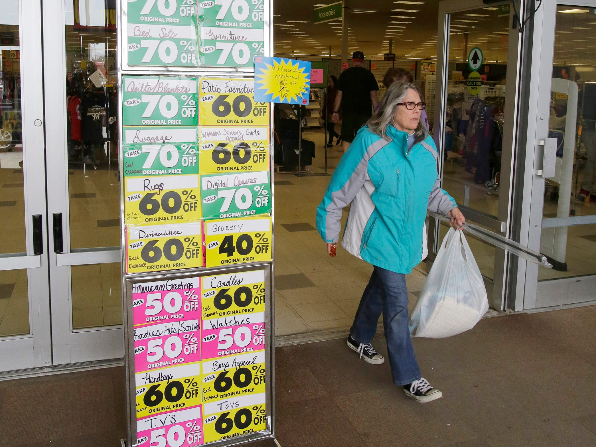 With signs indicating the closing store discounts, a woman leaves ShopKo with merchandise Saturday, May 11, 2019, in Sheboygan, Wis.