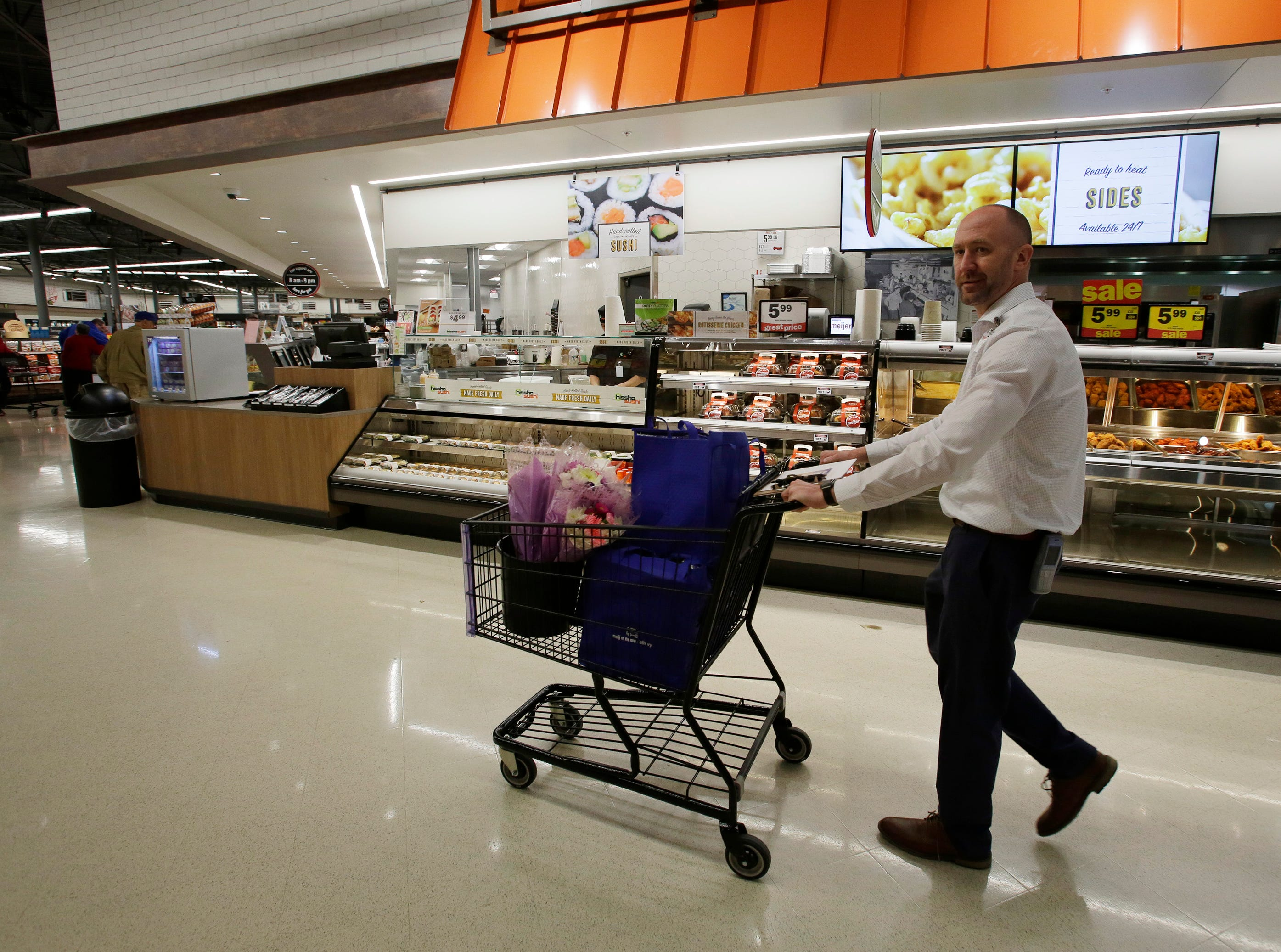 Store Director Jeff Kietzman pushes a cart of gifts for mothers at Meijer, Saturday, May 11, 2019, in Sheboygan, Wis. The store randomly selected moms and gave them a selection of gifts.