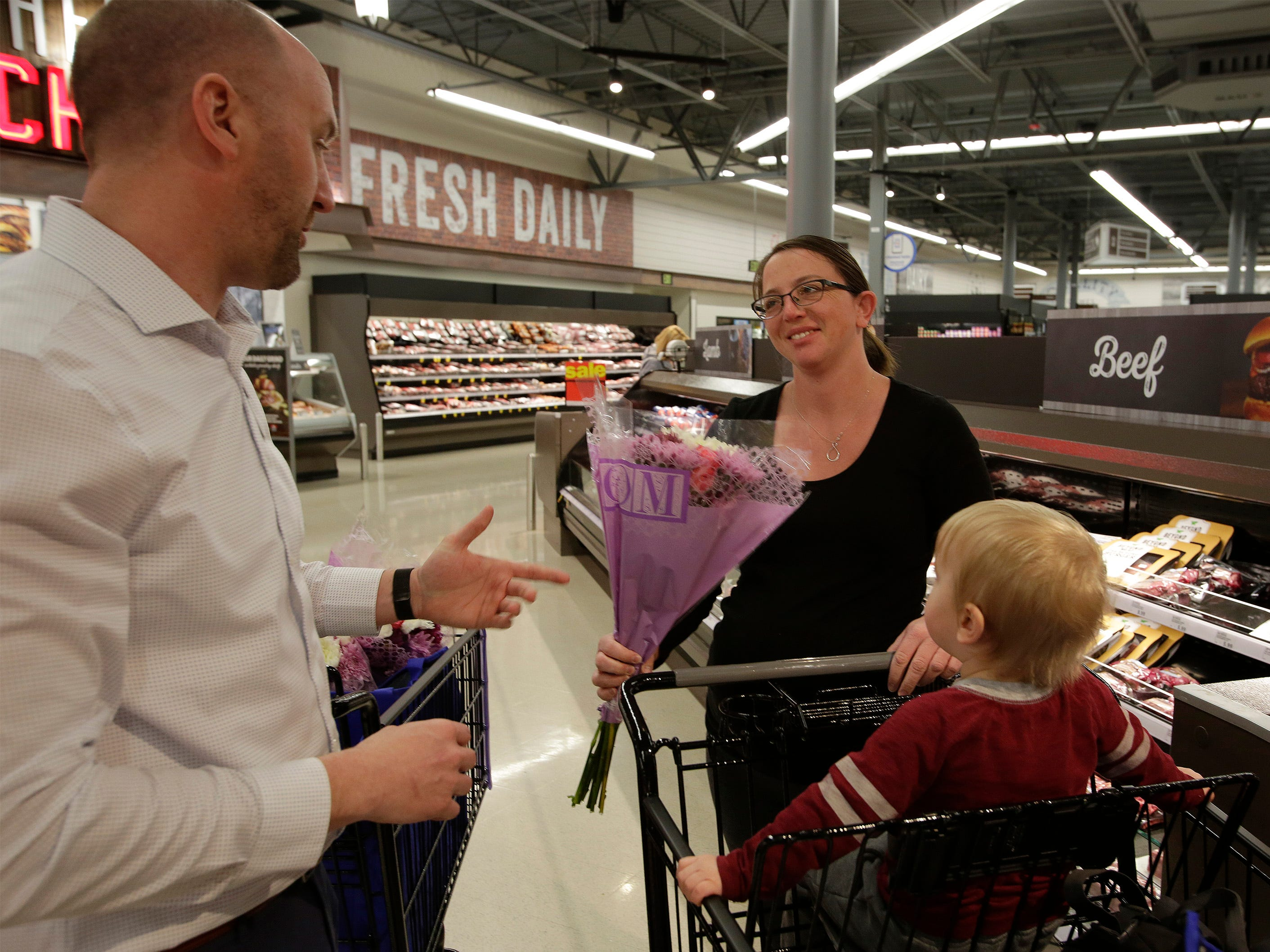 Tasha Peterson of Howards Grove, Wis., center, along with her son Lucas, 2, are presented flowers and gifts by Meijer Store Director Jeff  Kietzman, left, at Meijer, Saturday, May 11, 2019, in Sheboygan, Wis.