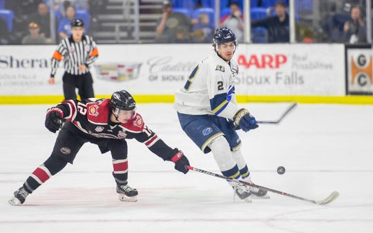 Steel forward Mathieu De St. Phalle knocks the puck away from Stampede defenseman Matt Kessel in game one of the Clark Cup finals on Friday, May 10, at the Sanford Premier Center in Sioux Falls.