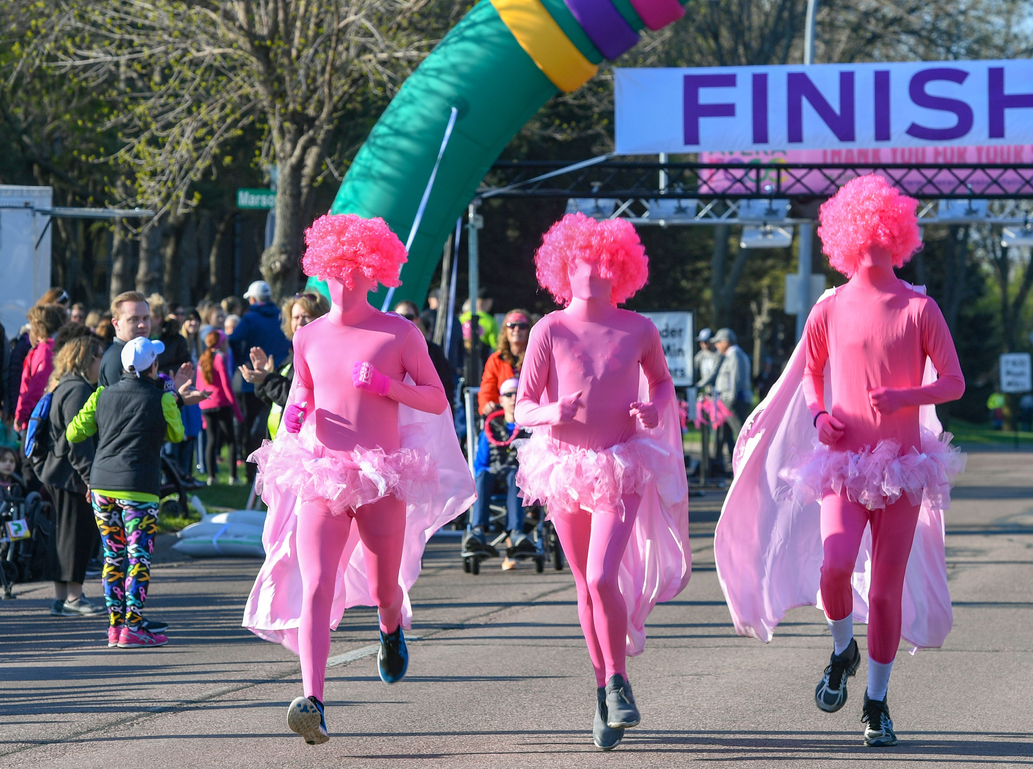 Runners in full pink costumes, including capes and wigs, bring up the rear in the 5K race at the 31st Avera Health Race Against Cancer on Saturday morning, May 11, in Sioux Falls.