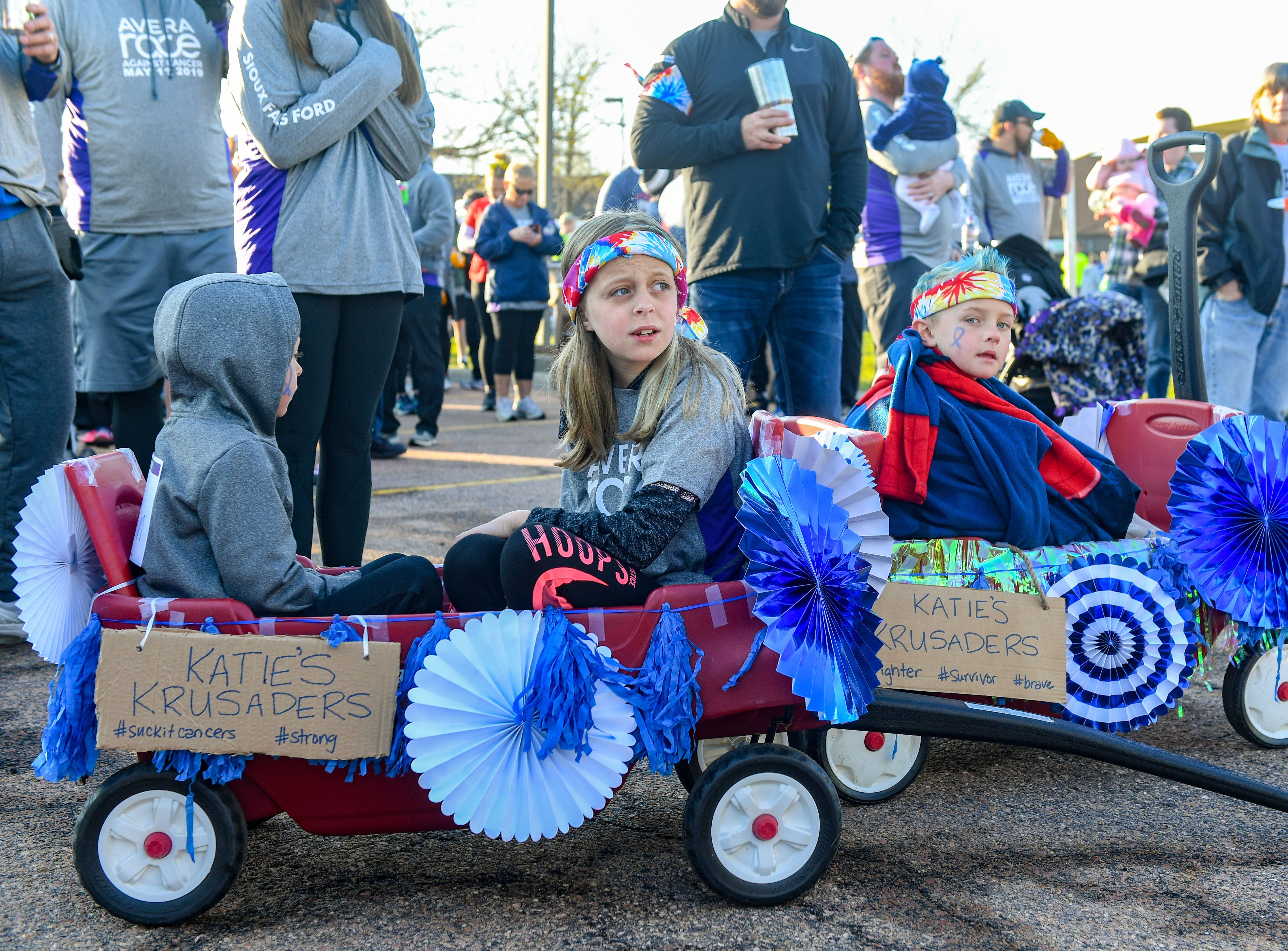 """""""Katie's Krusaders,"""" Brady and Jenna Jurgensen and Jake Jensen, sit in decorated wagons to watch the race at the 31st Avera Health Race Against Cancer on Saturday morning, May 11, in Sioux Falls."""