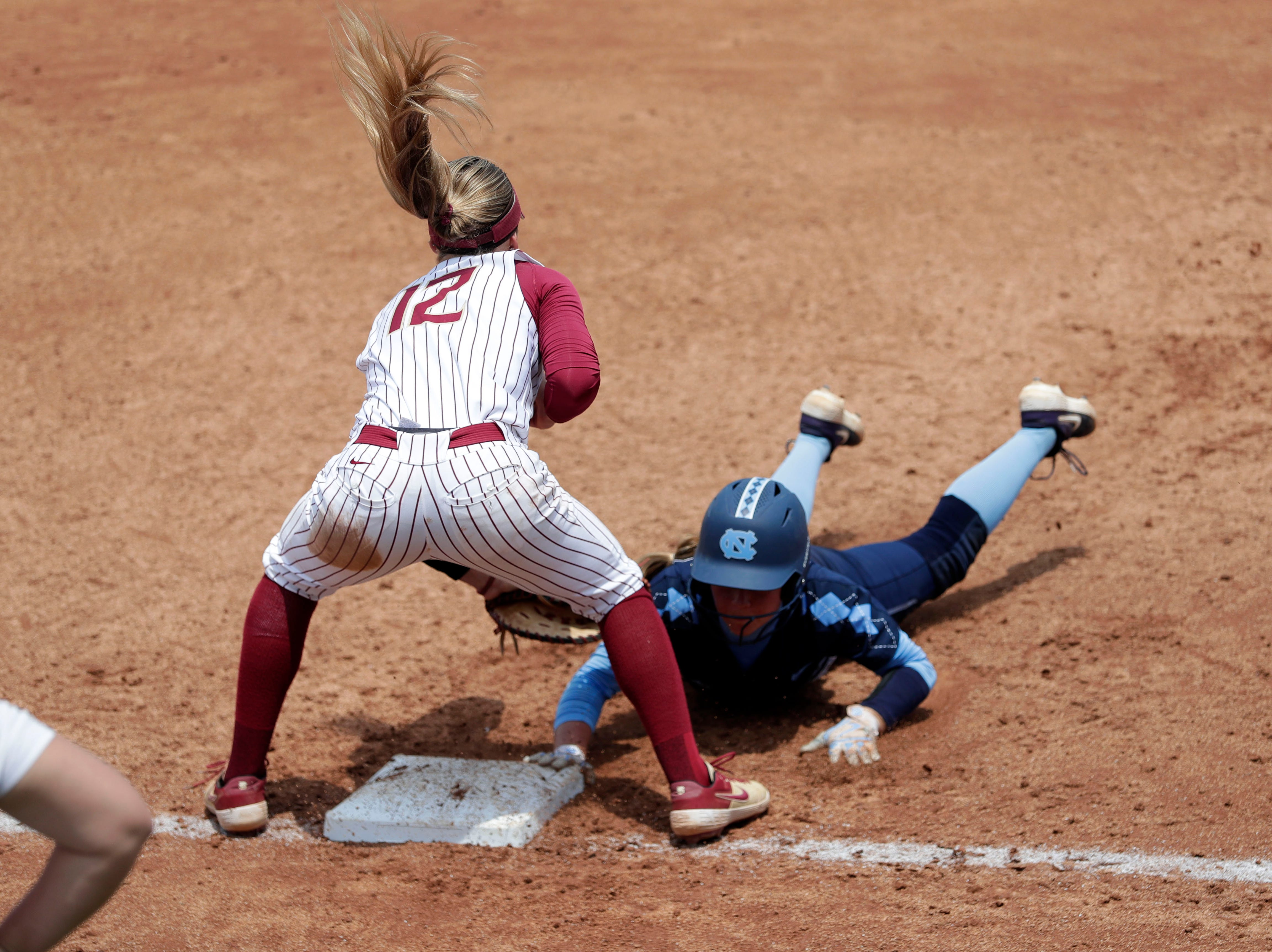 Florida State Seminoles infielder Carsyn Gordon (12) narrowly misses tagging the runner out at first. The Florida State Seminoles host the UNC Tar Heels for the ACC Softball Tournament finals Saturday, May 11, 2019.