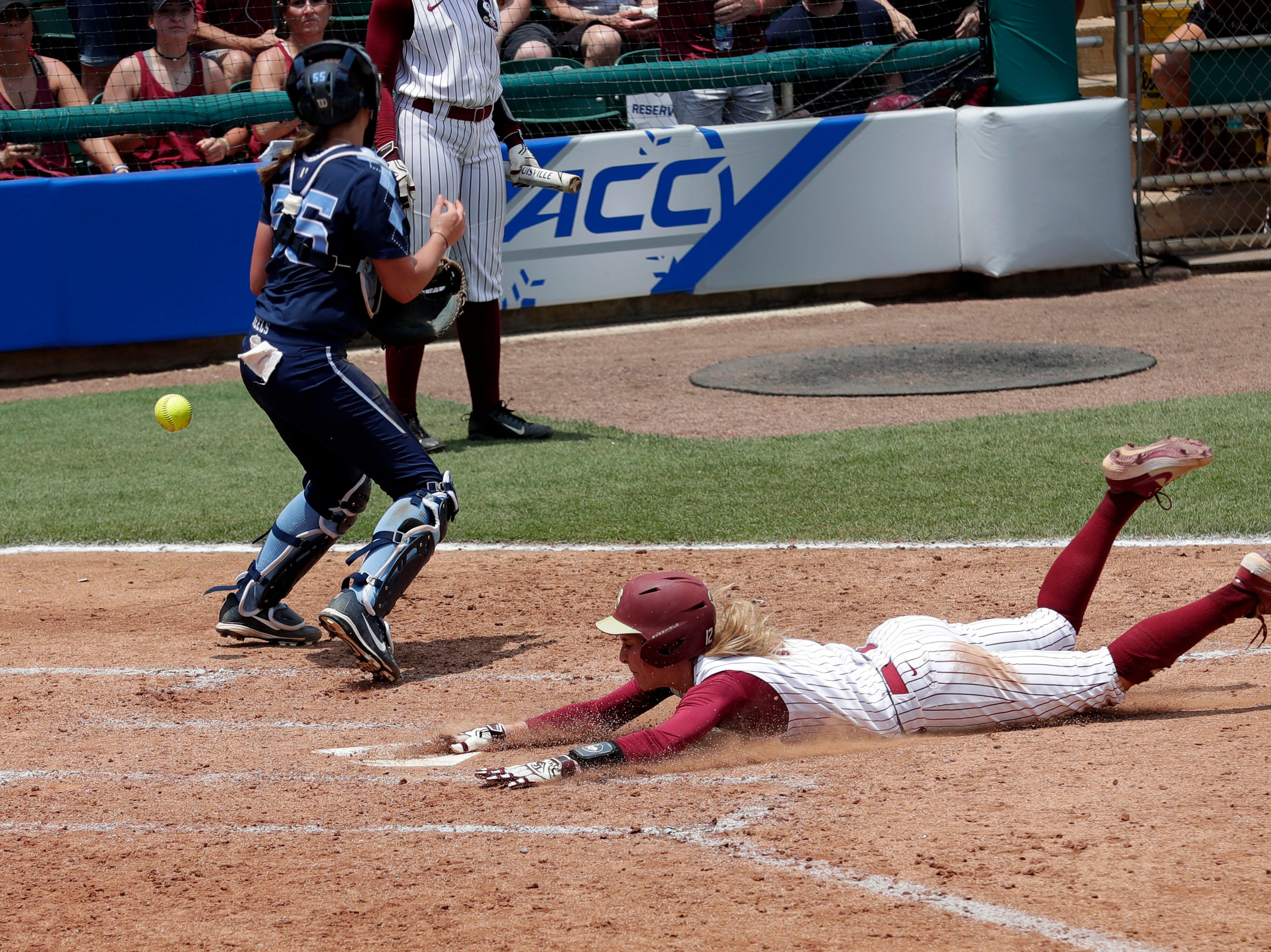 Florida State Seminoles infielder Carsyn Gordon (12) slides into home plate to score. The Florida State Seminoles host the UNC Tar Heels for the ACC Softball Tournament finals Saturday, May 11, 2019.