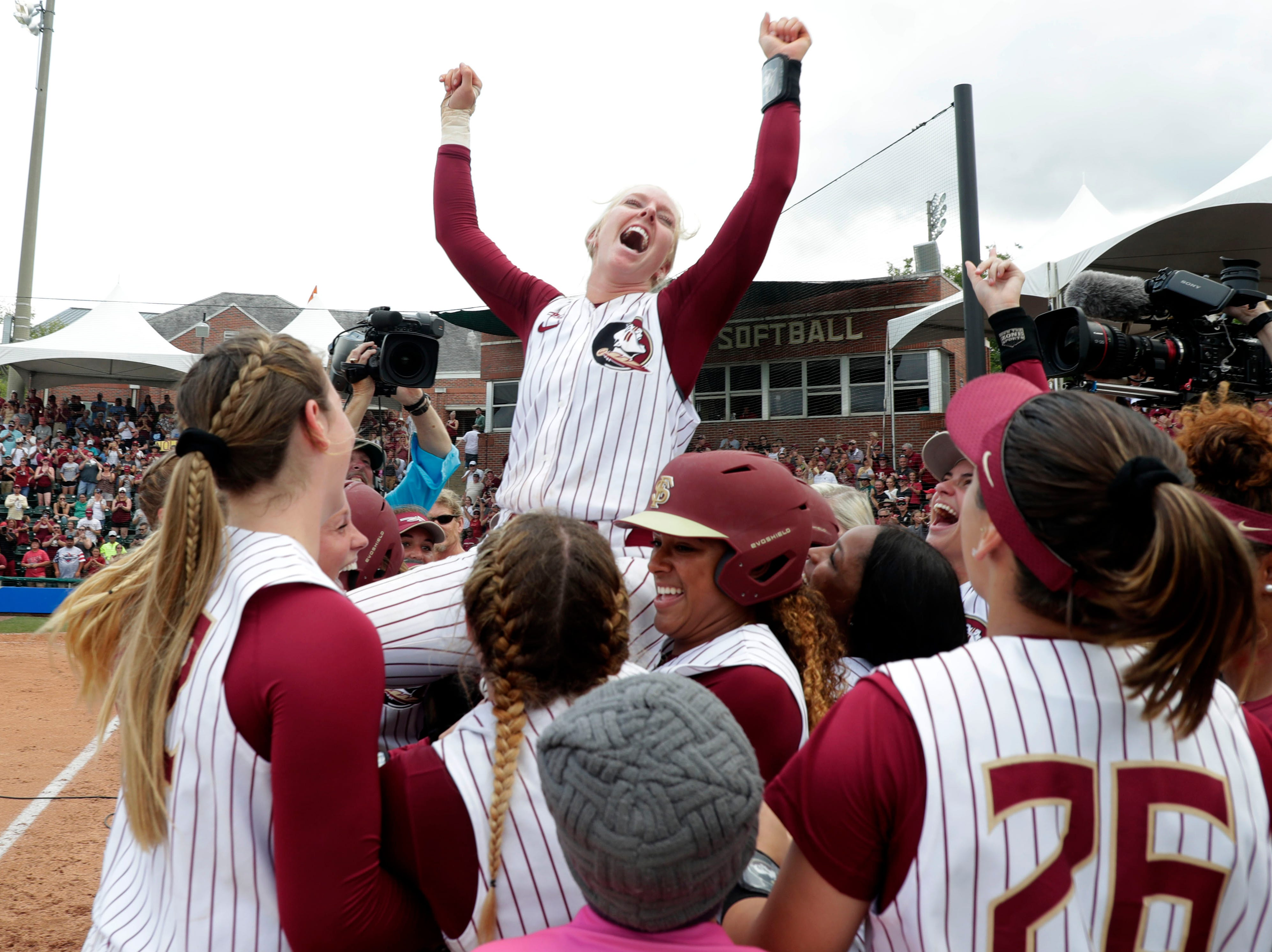 Florida State Seminoles utility player Sydney Sherrill (24) is lifted up by her teammates. The Florida State Seminoles celebrate their victory over the UNC Tar Heels for the ACC Softball Championship title Saturday, May 11, 2019.