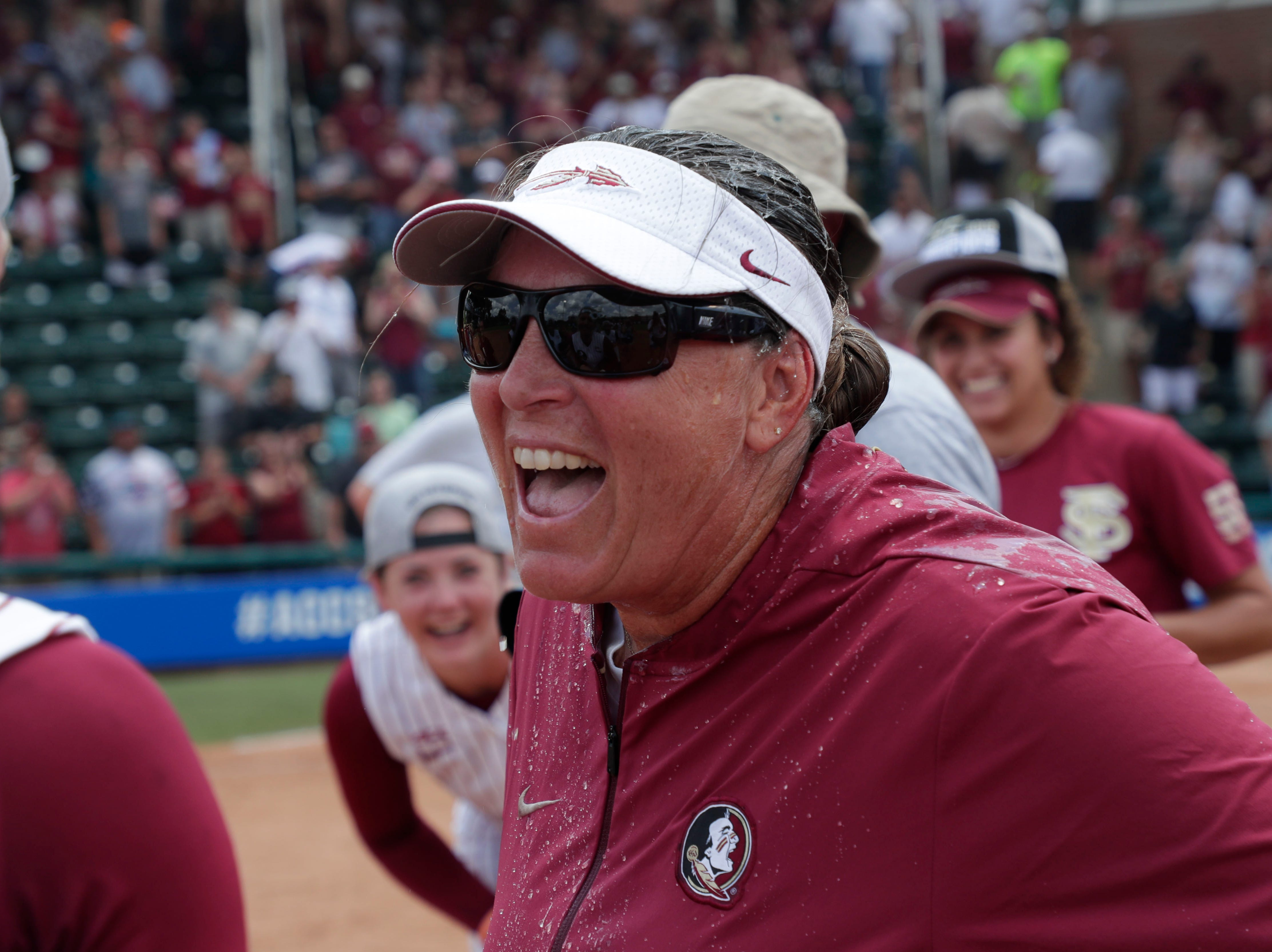 Florida State Seminoles head coach celebrates her team's big win with the players. The Florida State Seminoles celebrate their victory over the UNC Tar Heels for the ACC Softball Championship title Saturday, May 11, 2019.