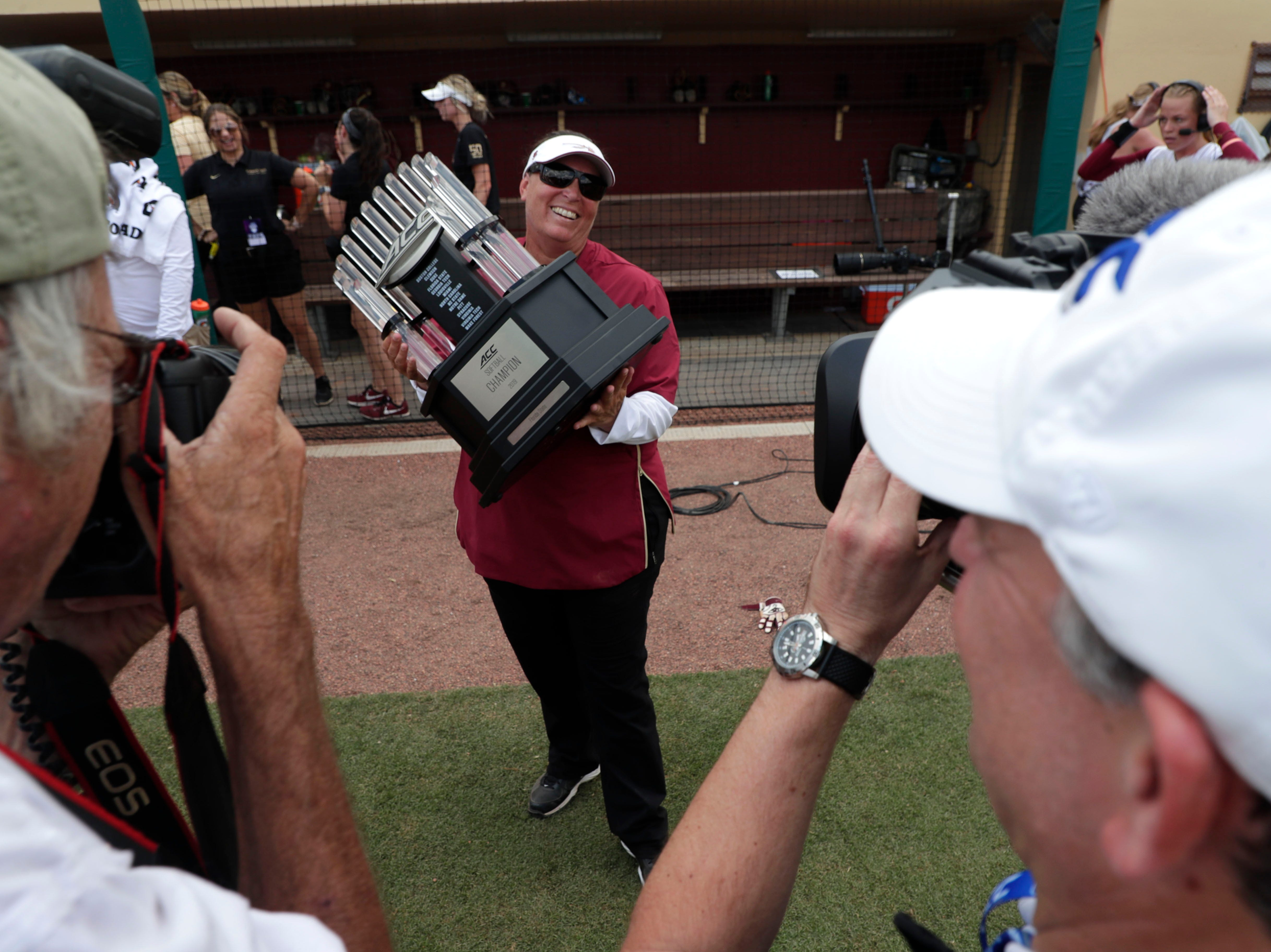 Florida State Seminoles head coach Lonni Alameda holds the championship trophy. The Florida State Seminoles celebrate their victory over the UNC Tar Heels for the ACC Softball Championship title Saturday, May 11, 2019.
