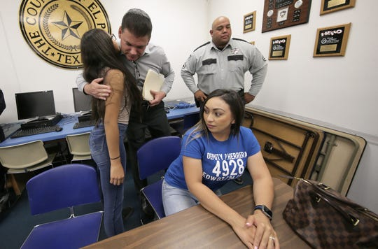 El Paso County Sheriff Richard Wiles hugs Dep. Peter Herrera's daughter Natalie Maldonado before holding a press conference to announce a second arrest in her father Dep. Peter Herrera's death. Herrera's wife Ashley Herrera, right, attended with family members to hear the news.
