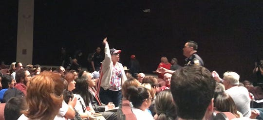 """El Pasoan Lily Madrid yells, """"America first,"""" as she is escorted out by El Paso police during U.S. Rep Veronica Escobar's town hall meeting Saturday, May 11, 2019, at Canutillo High School."""