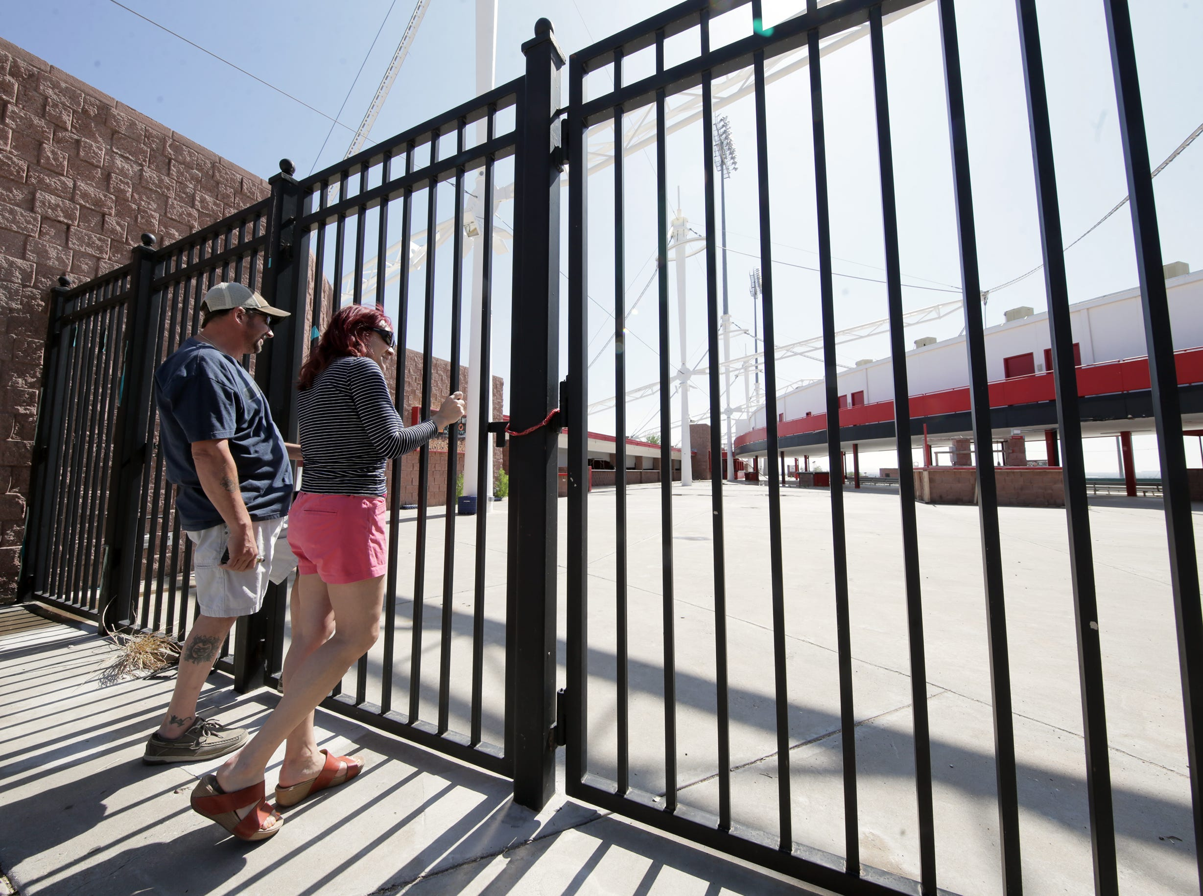 Mike Tocchetti and Christina Maxwell look through the gates at Cohen Stadium during Selfie Day at Cohen Stadium on Saturday, May 11, 2019, before demolition begins.