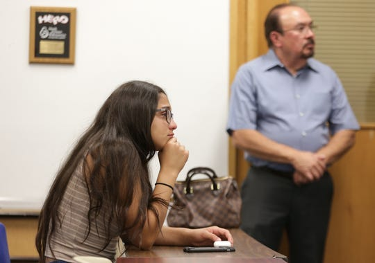 Natalie Maldonado, daughter of Sheriff Dep. Peter Herrera who was killed in the line of duty, cries as El Paso County Sheriff Richard Wiles announces a second arrest in the murder of her father.
