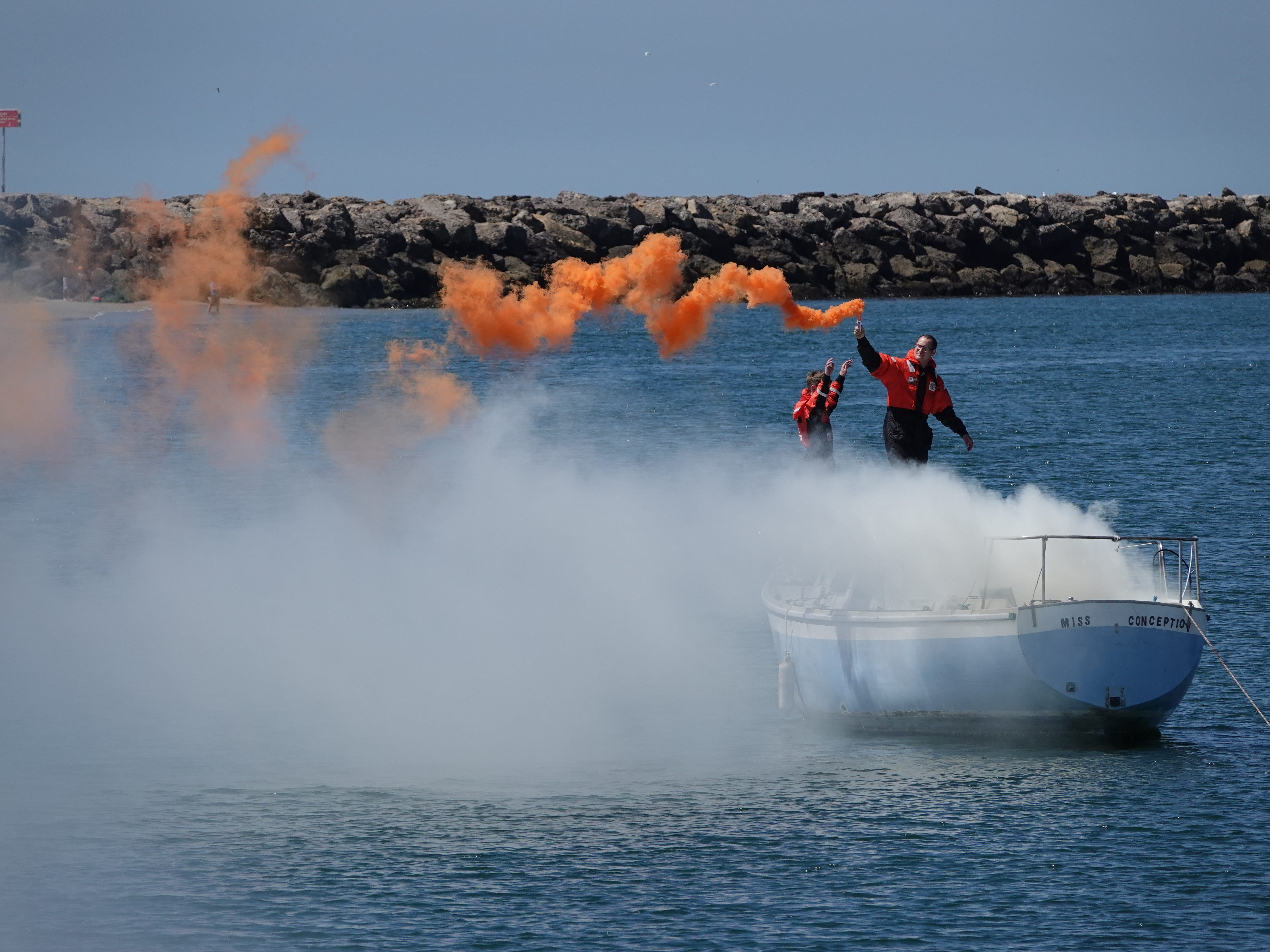 A flare held by U.S. Coast Guard Seaman Charles Hubbard signals trouble during a mock rescue Saturday  during the Safe Boating Expo at Channel Islands Harbor in Oxnard.