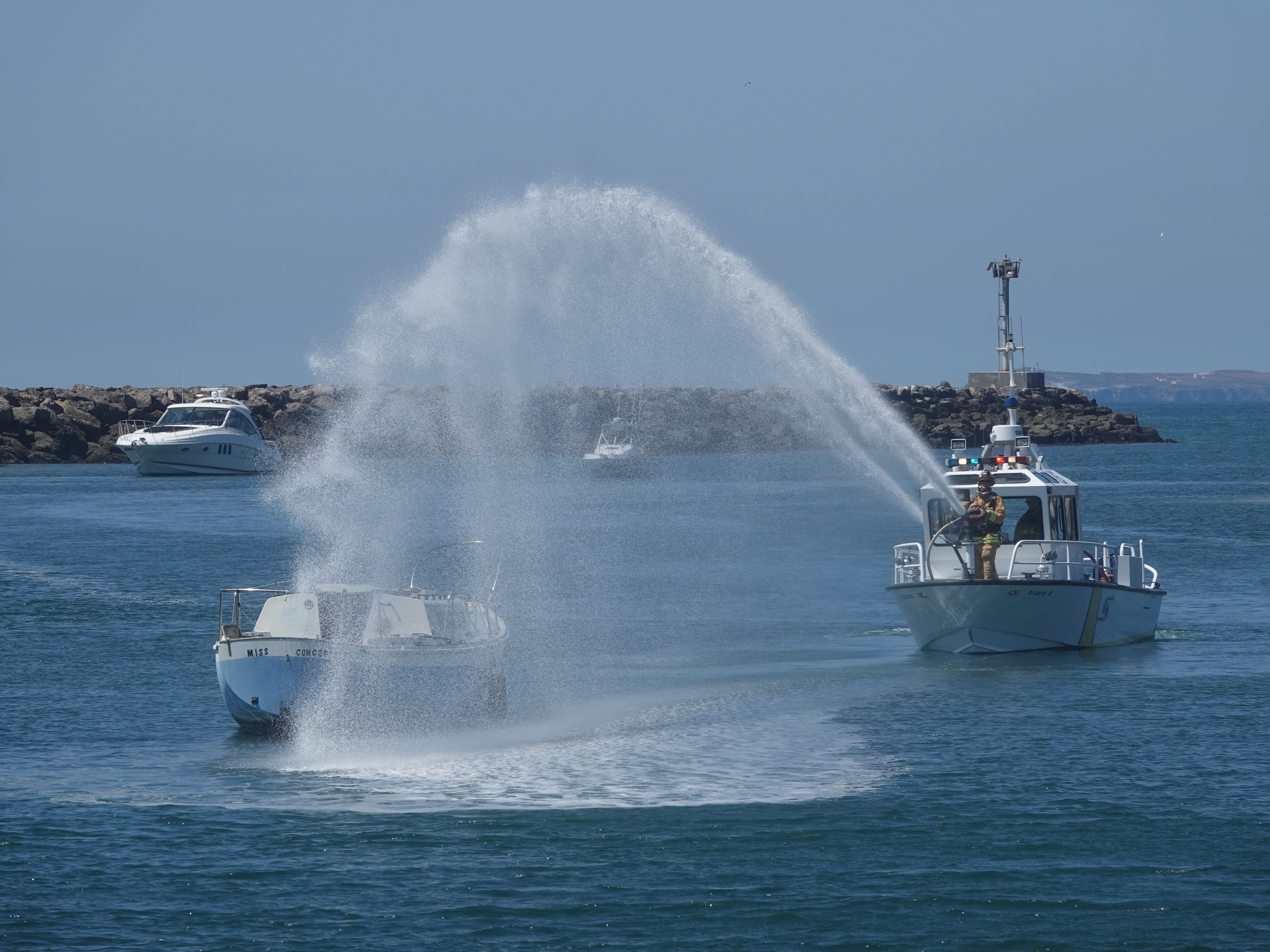 A plume of water douses a small craft during a rescue demonstration Saturday at the Coast Guard's Safe Boating Expo at Channel Islands Harbor.