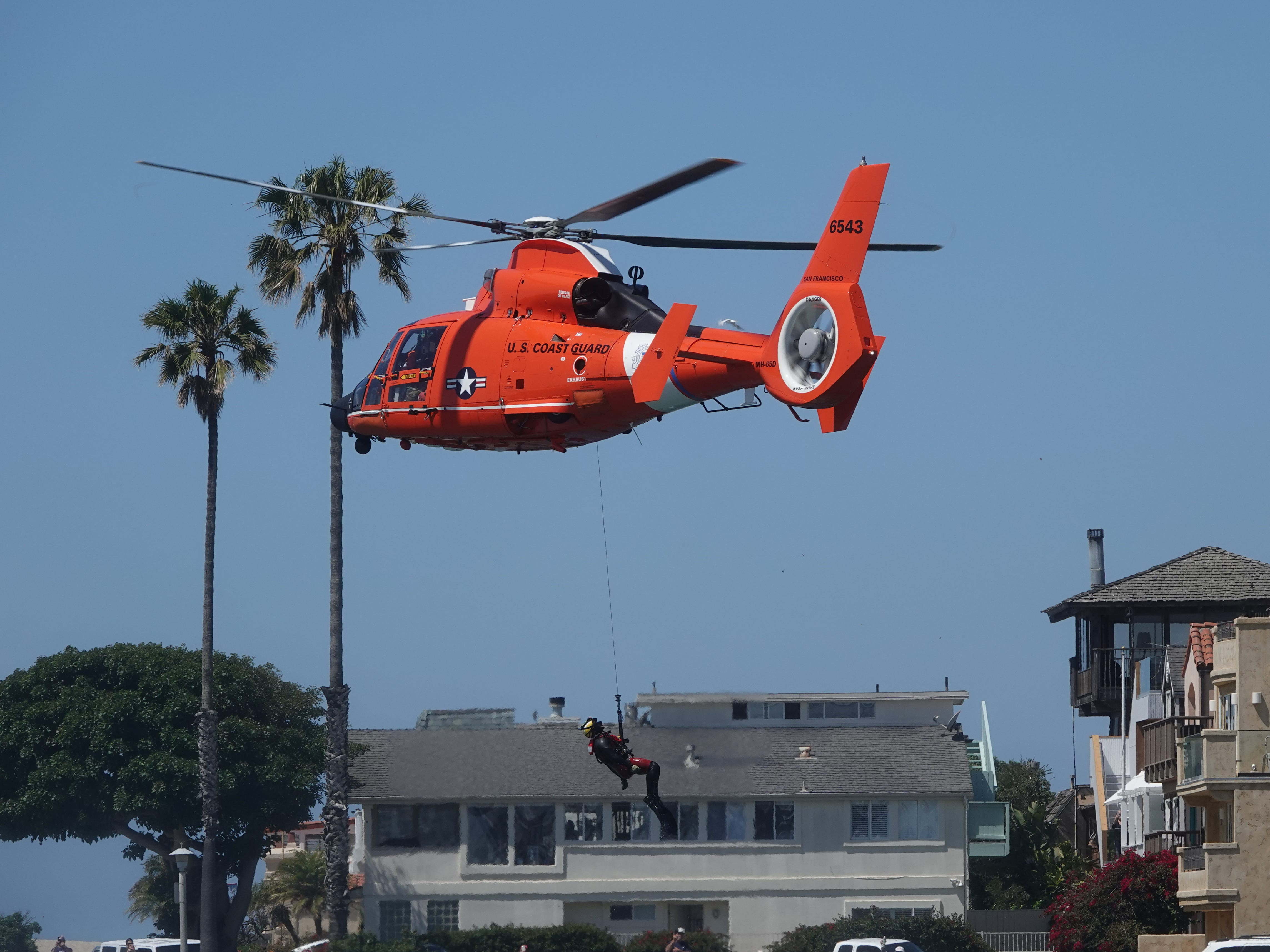 A U.S. Coast Guard rescue swimmer is hoisted into a helicopter after a mock rescue during the Safe Boating Expo at Channel Islands Harbor in Oxnard Saturday.