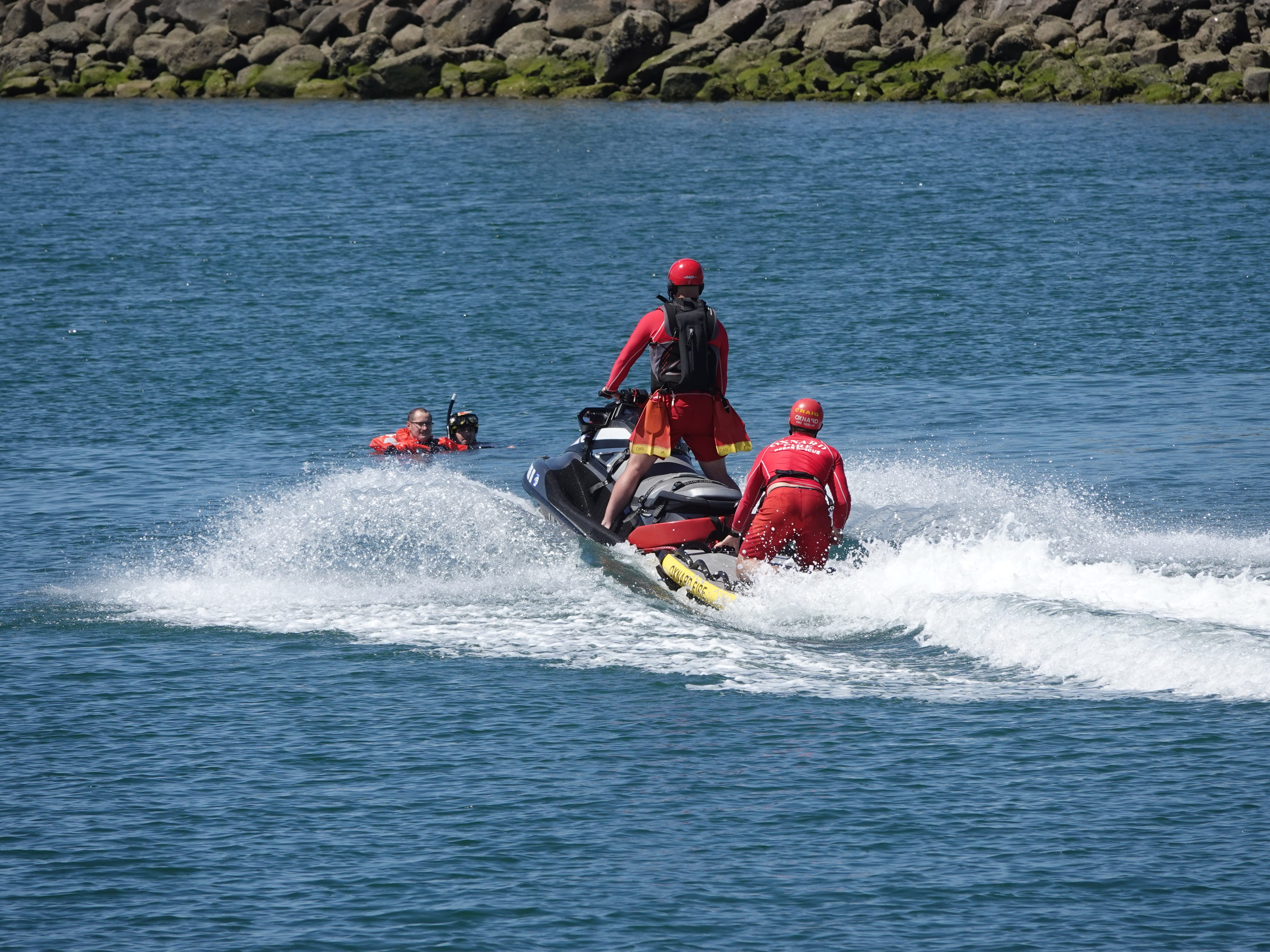 Oxnard firefighters race toward a mock boating victim during a rescue demonstration Saturday at the 14th annual Safe Boating Expo at Channel Islands Harbor.