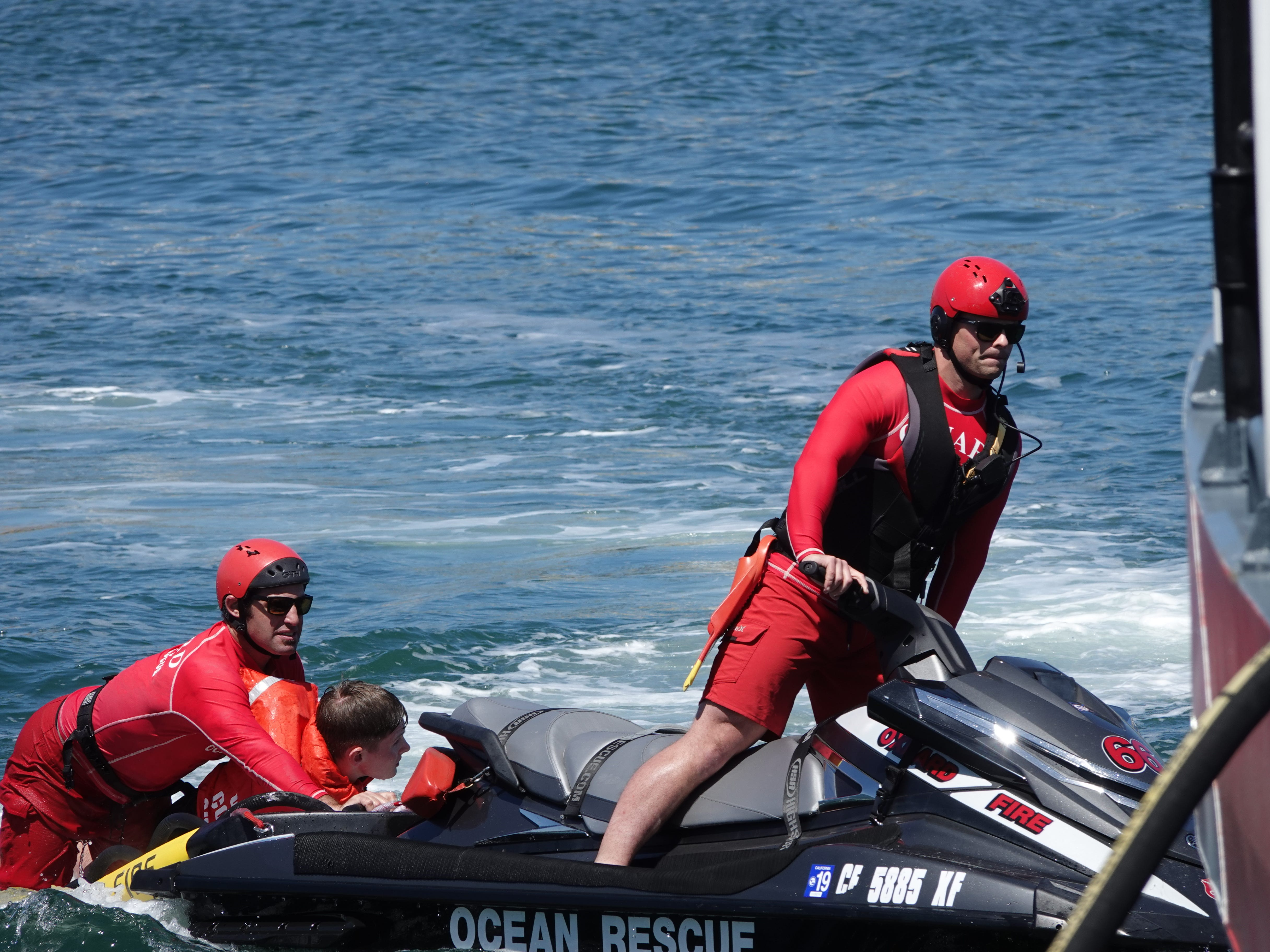 Oxnard firefighters carry Finn-Christian Baker, a mock victim, to safety during Saturday's Safe Boating Expo at Channel Islands Harbor.