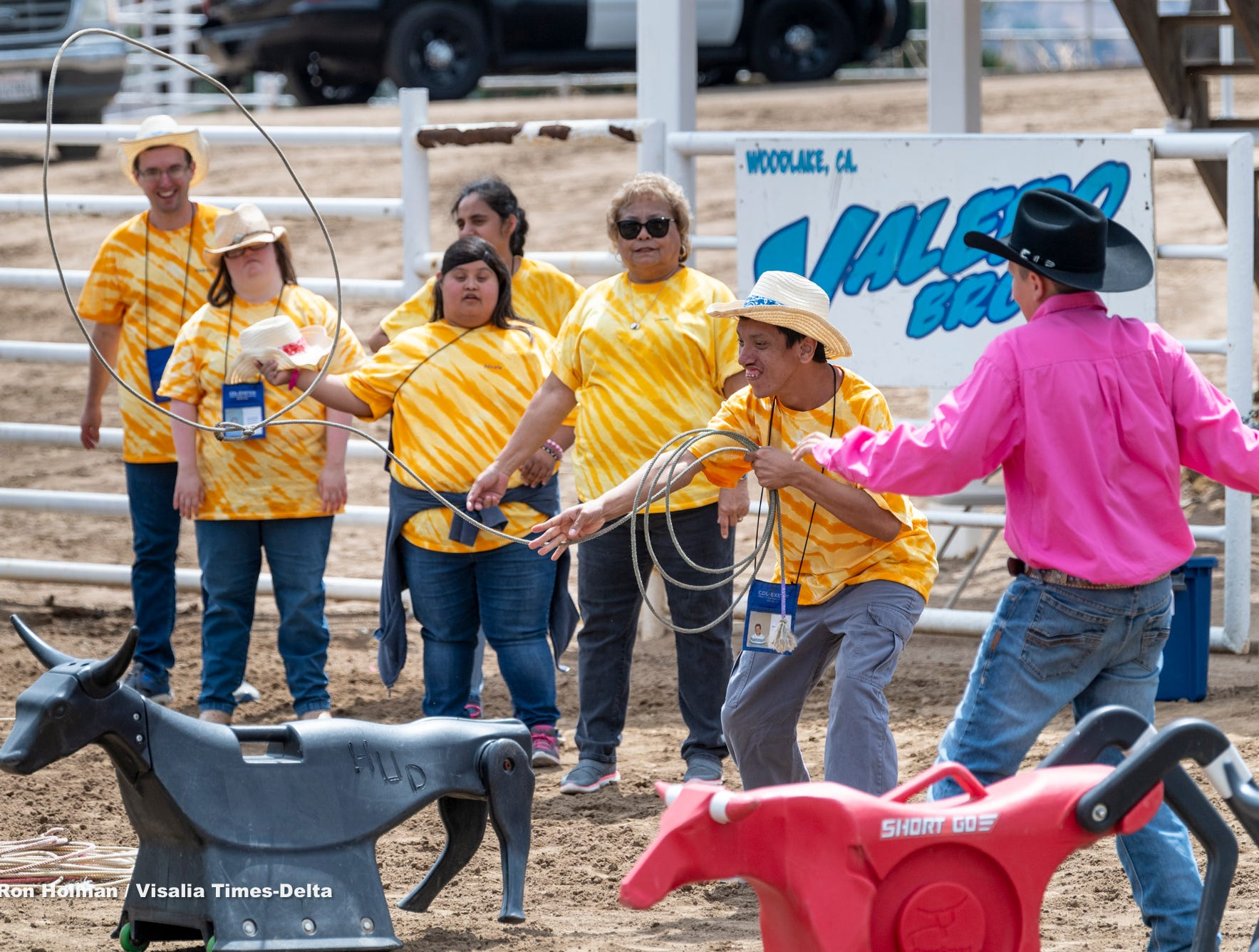"""Wyatt Rose, right, helps Francisco Chavez learn to rope during the first """"High-Five Rodeo"""" at the Woodlake Rodeo Grounds on Friday, May 10, 2019. Participants from Exeter's Center for Discovery and Learning were paired up with real-life cowboys and cowgirls and other performers to experience modified rodeo-related stations in the rodeo arena."""