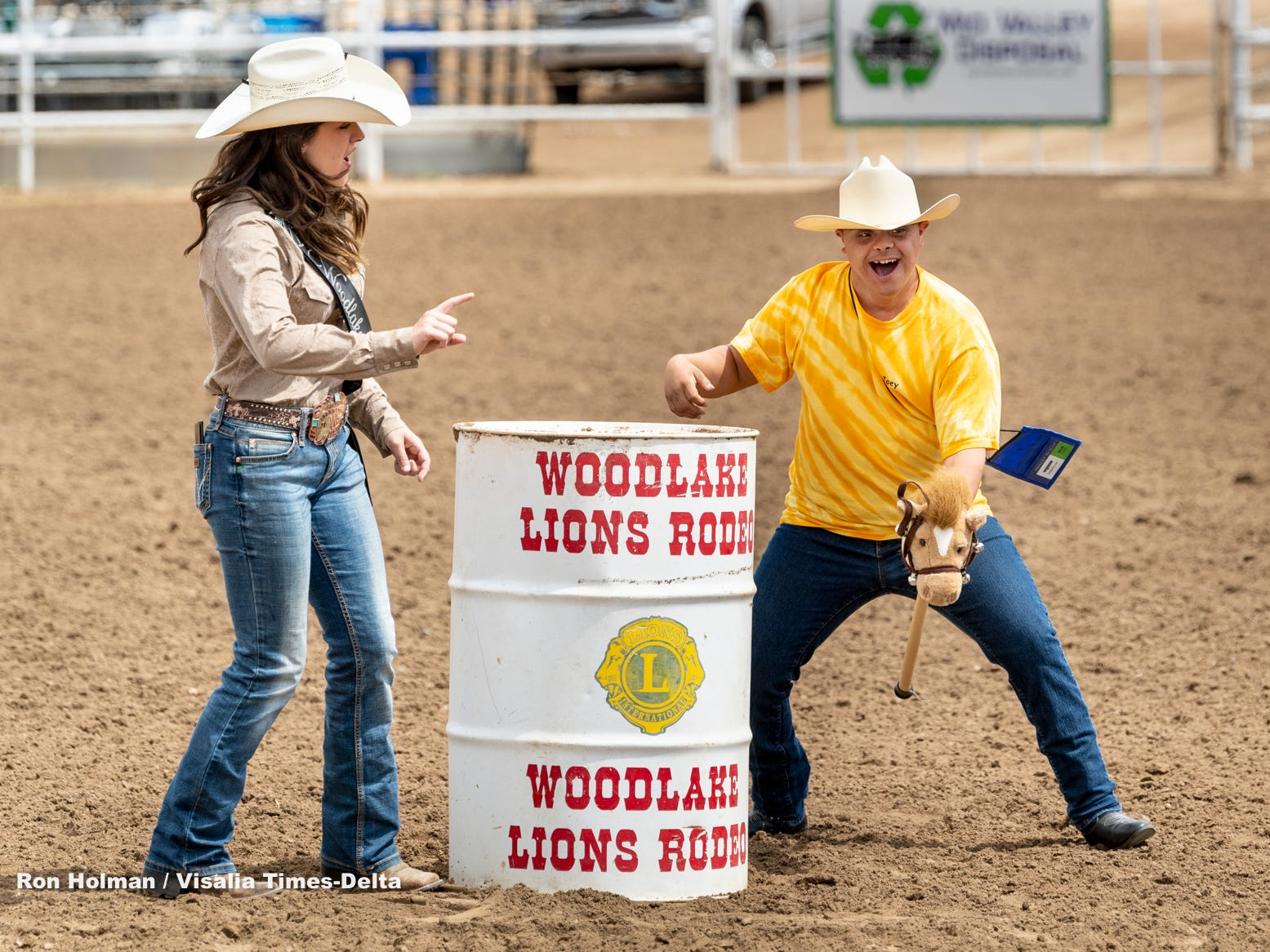 """Mallory McLaughlin, left, directs participants through a barrel race during Woodlake Rodeo first """"High-Five Rodeo"""" on Friday, May 10, 2019. Participants from Exeter's Center for Discovery and Learning were paired up with real-life cowboys and cowgirls and other performers to experience modified rodeo-related stations in the rodeo arena."""
