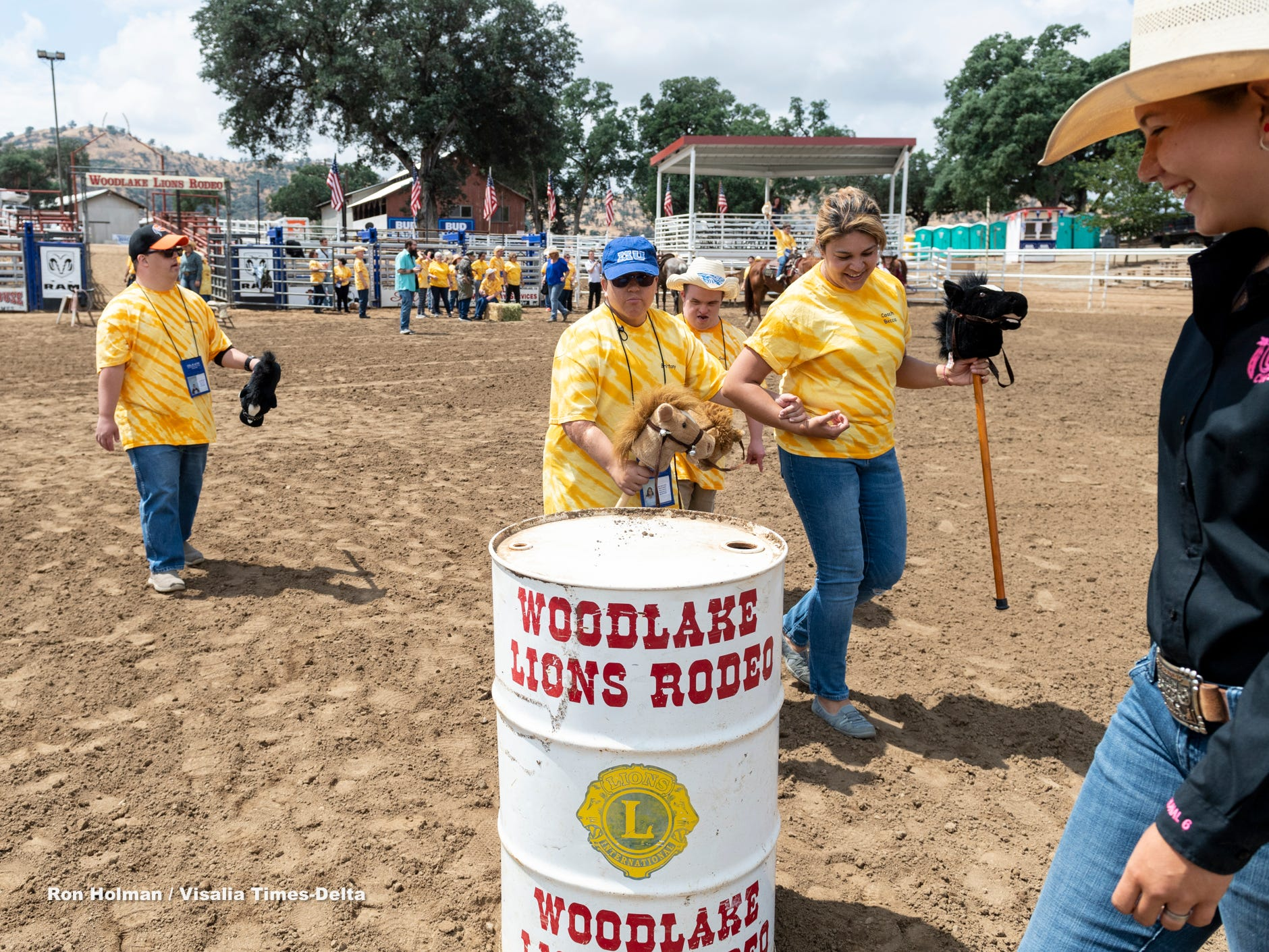"""Ellie Bonilla, right, leads staff and clients through a barrel race during the first """"High-Five Rodeo"""" at the Woodlake Rodeo Grounds on Friday, May 10, 2019. Participants from Exeter's Center for Discovery and Learning were paired up with real-life cowboys and cowgirls and other performers to experience modified rodeo-related stations in the rodeo arena."""