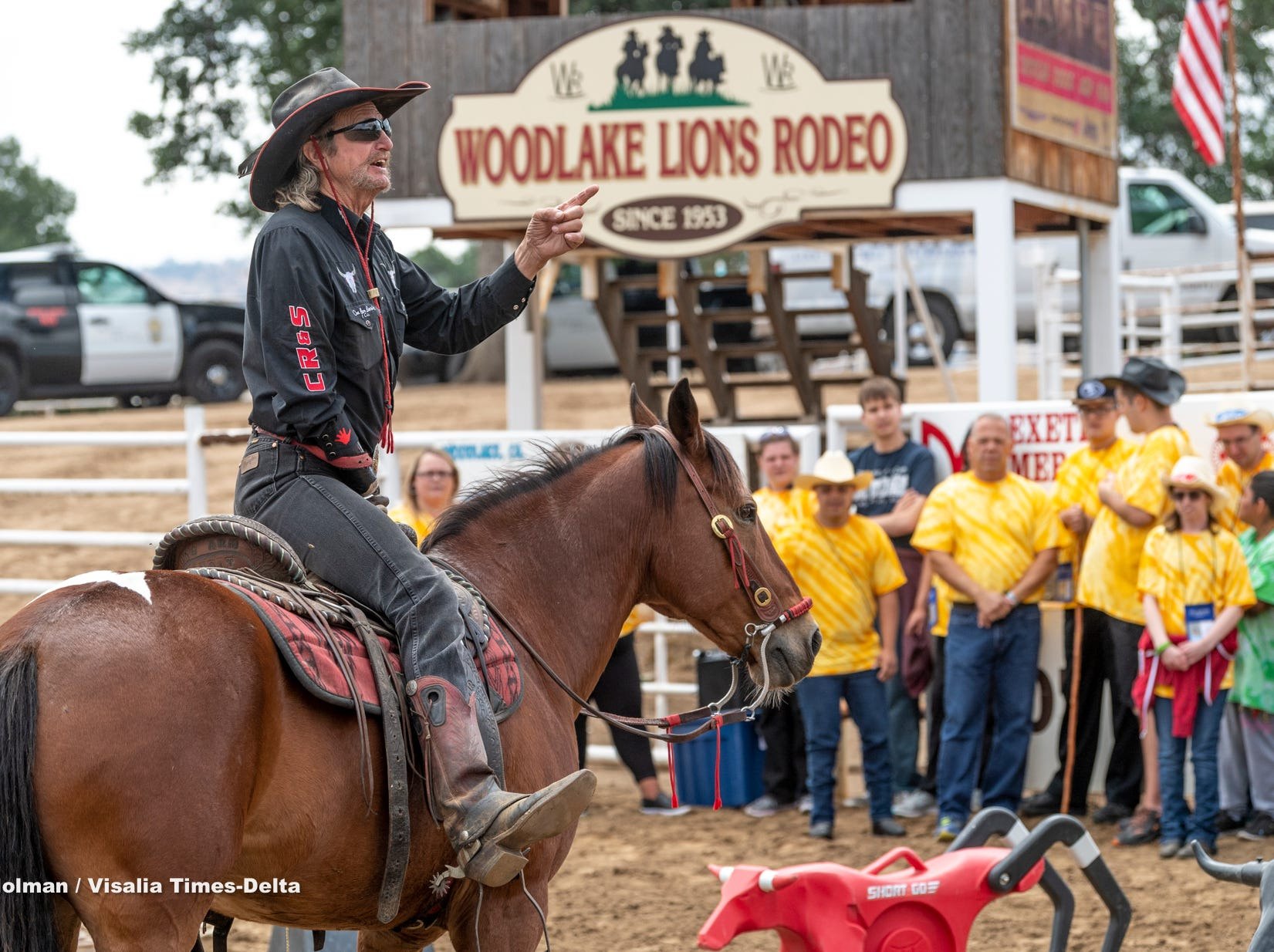 """John Lynn, The One Arm Bandit, talks to clients from Exeter's Center for Discovery and Learning during The Woodlake Rodeo's first """"High-Five Rodeo"""" on Friday, May 10, 2019. Participants were paired up with real-life cowboys and cowgirls and other performers to experience modified rodeo-related stations in the rodeo arena."""