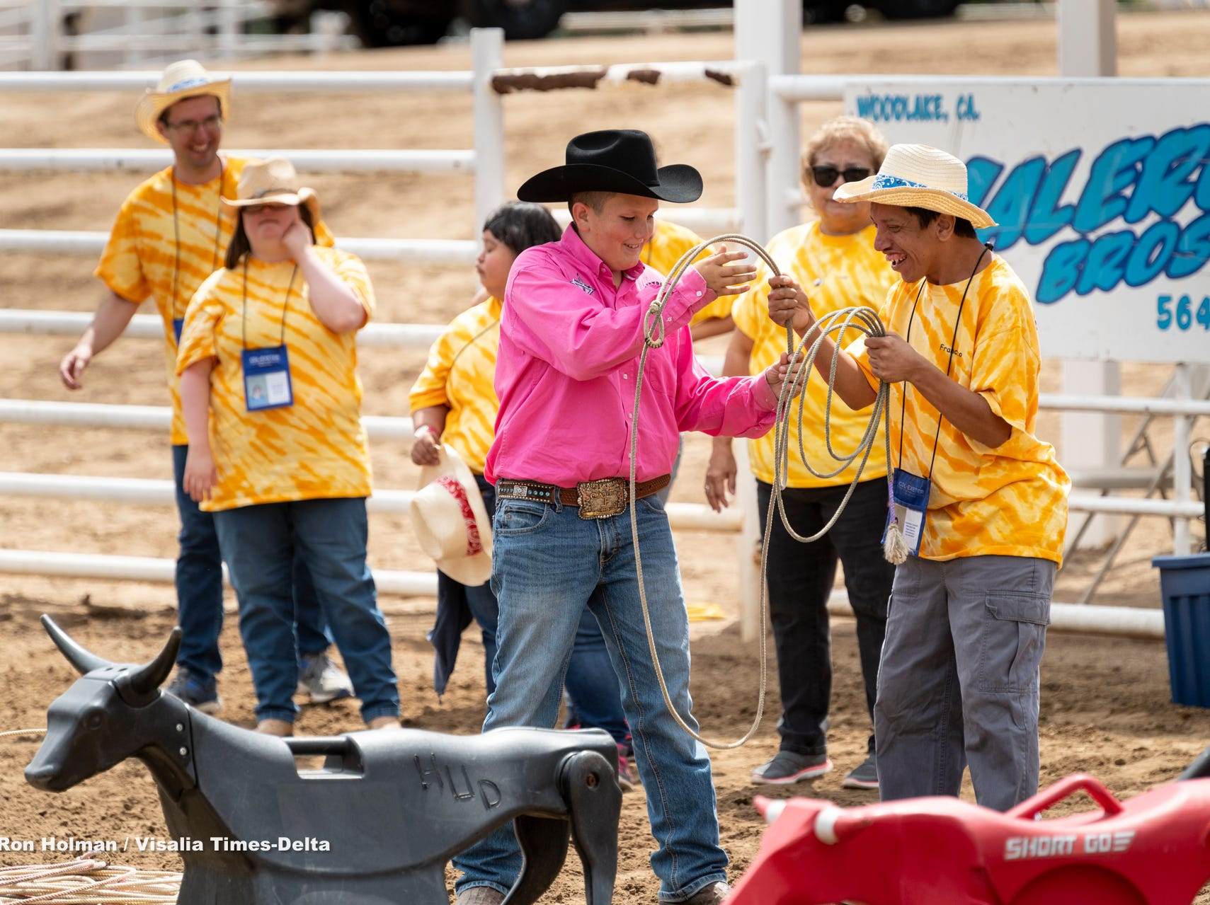 """Francisco Chavez, right, gets a roping lesson from Wyatt Rose during the first """"High-Five Rodeo"""" at the Woodlake Rodeo Grounds on Friday, May 10, 2019. Participants from Exeter's Center for Discovery and Learning were paired up with real-life cowboys and cowgirls and other performers to experience modified rodeo-related stations in the rodeo arena."""