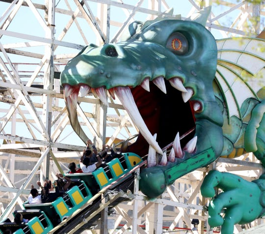 Riders raise their arms and scream as they ride the Dragon Coaster during opening day at Playland in Rye, May 11, 2019.