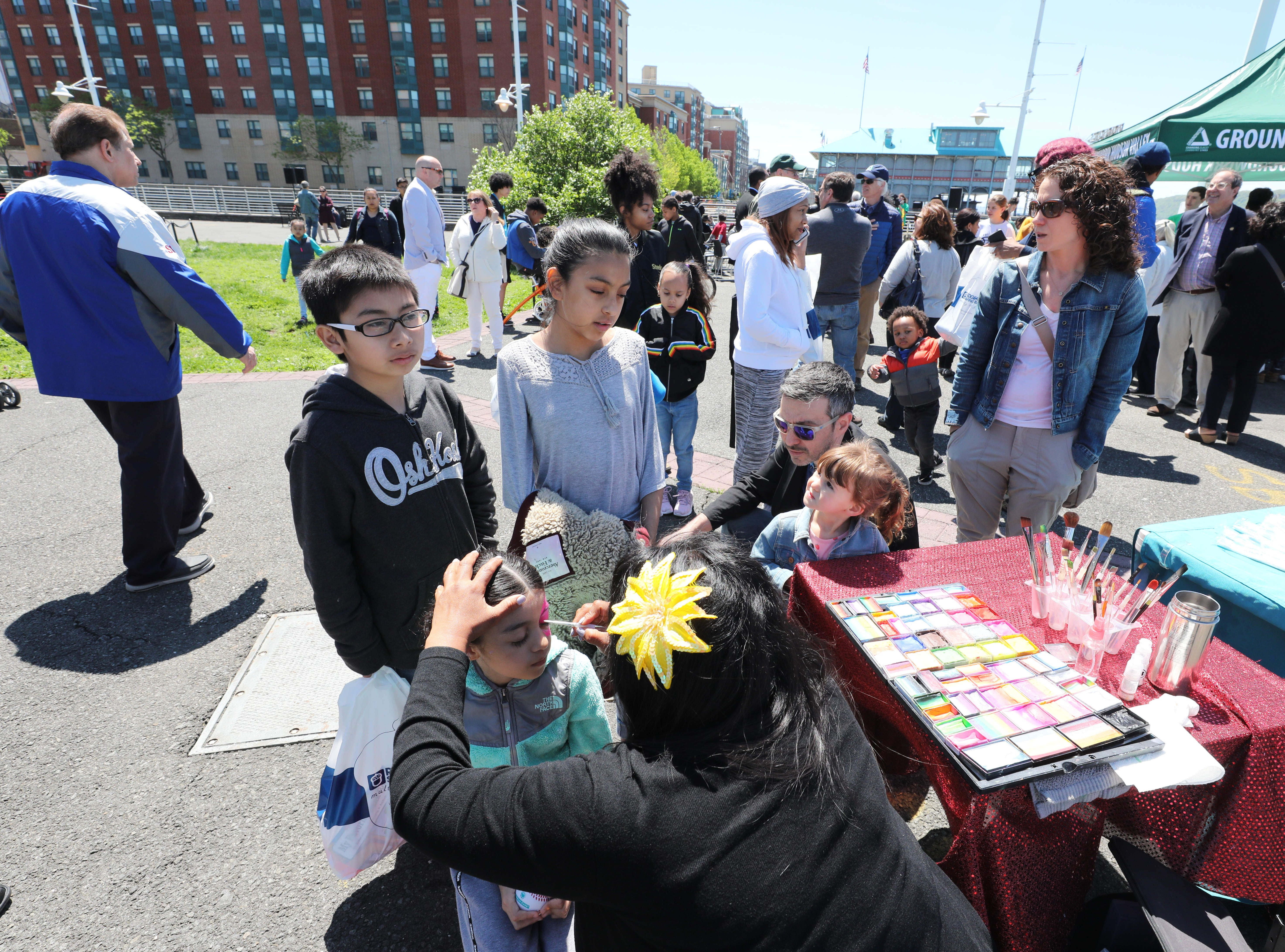 Kids have their faces painted during the 11th annual opening of the Science Barge  on the Hudson River in Yonkers, May 11, 2019. The floating environmental education center has undergone an almost $1million enhancement, completed over the past two years.