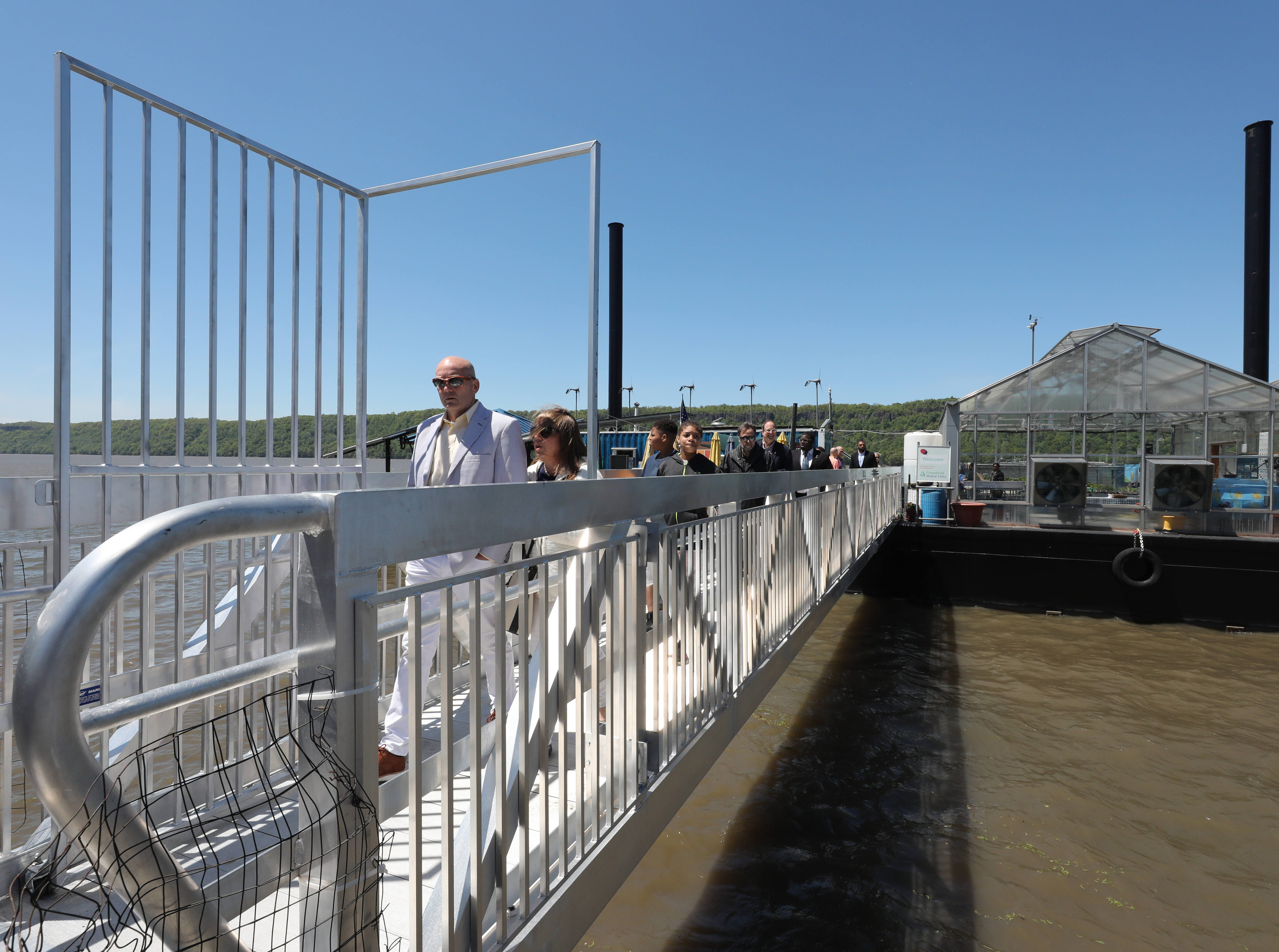 People walk along the brand new gangway and gate as the Science Barge enjoys its 11th annual opening on the Hudson River in Yonkers, May 11, 2019. The floating environmental education center  has undergone an almost $1million enhancement, completed over the past two years.