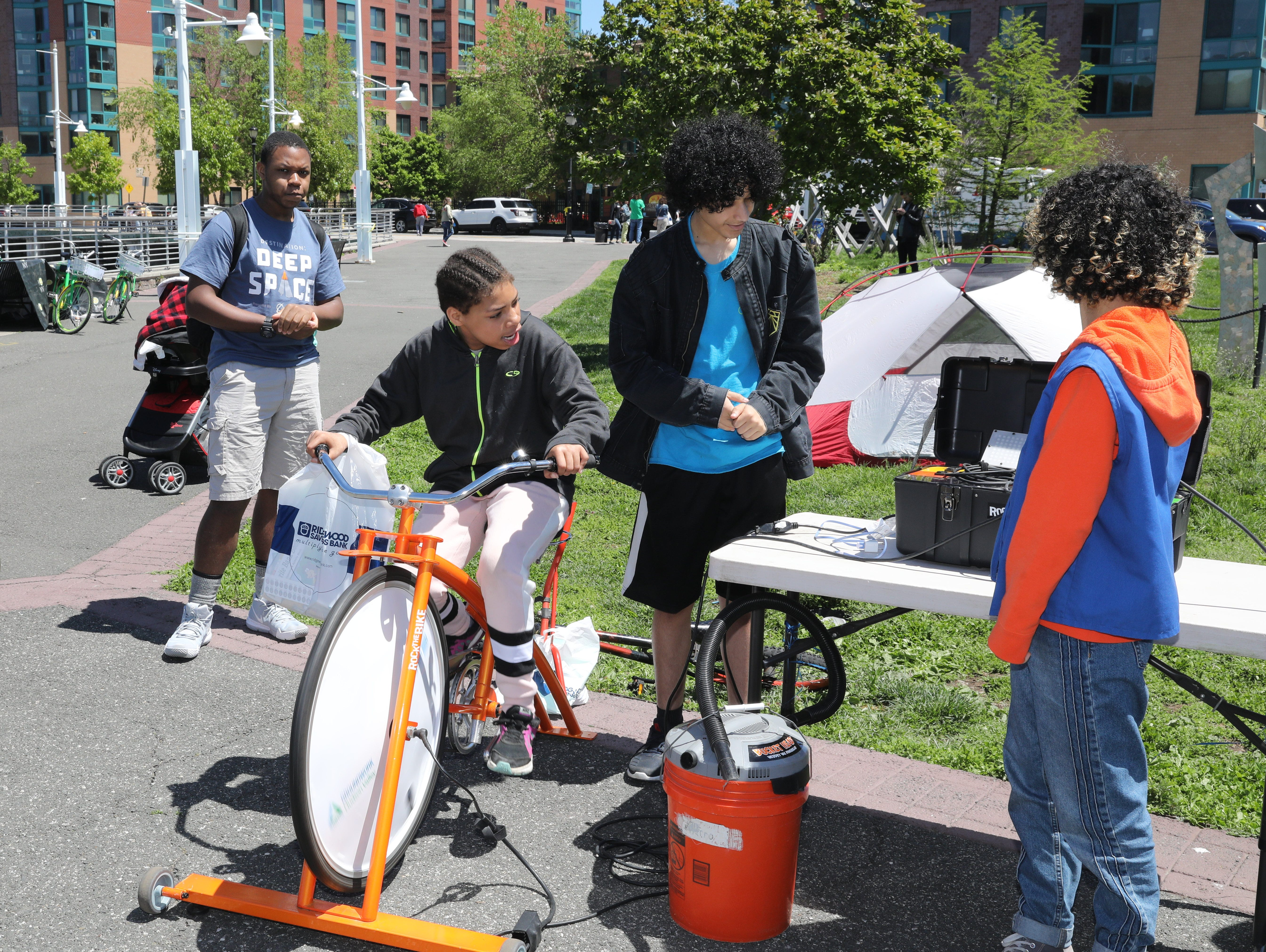 Children make some energy using a bicycle, during the opening of the Science Barge at its 11th annual opening on the Hudson River in Yonkers, May 11, 2019. The floating environmental education center  has undergone an almost $1million enhancement, completed over the past two years.