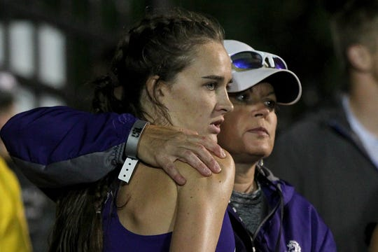 Benjamin's Temi Flowers is hugged by her mom and coach Mindy Myers after Friday's mile relay.