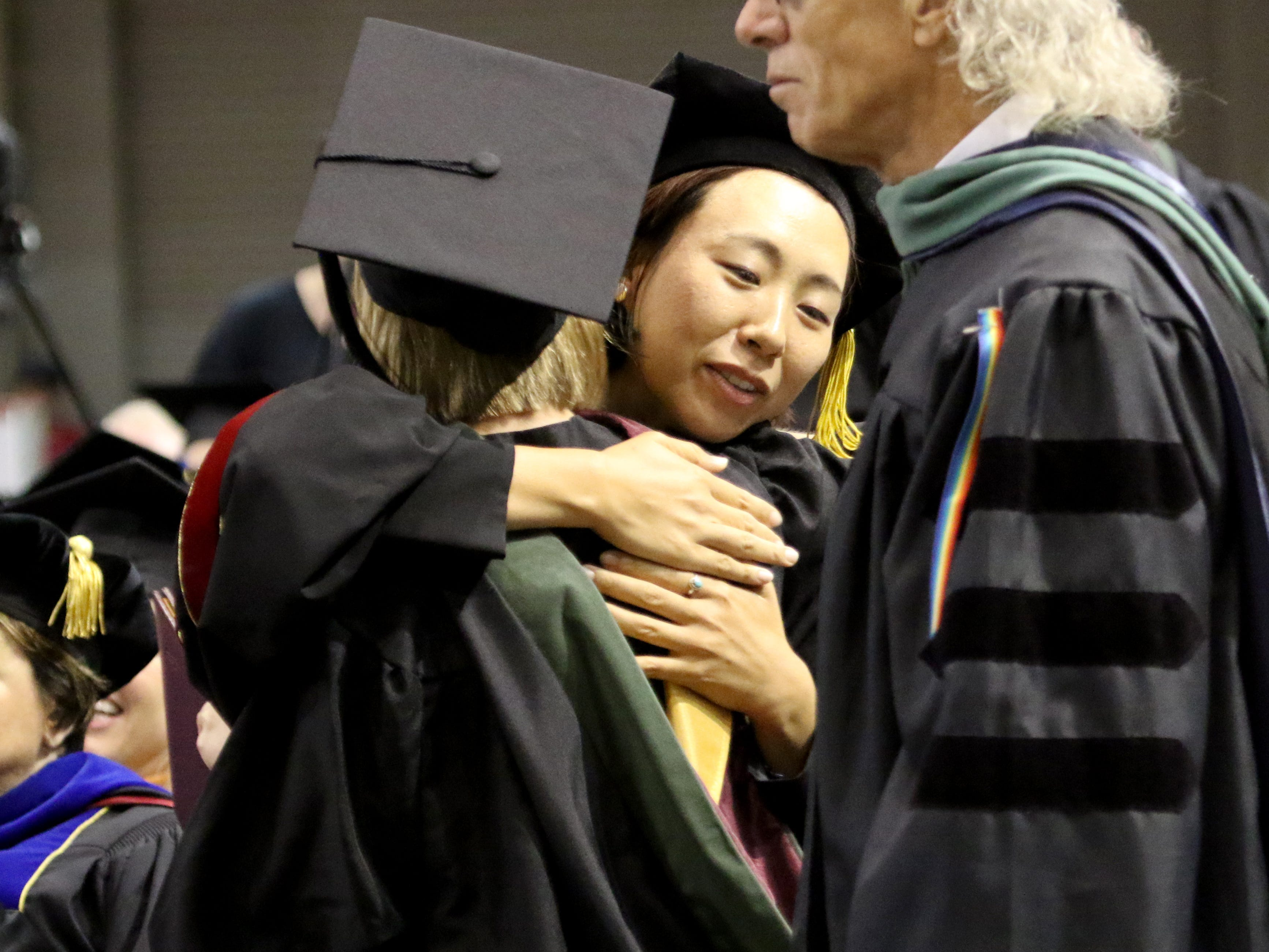 Professors hug their graduates at Midwestern State University's Spring Commencement Saturday, May 11, 2019, in Kay Yeager Coliseum.