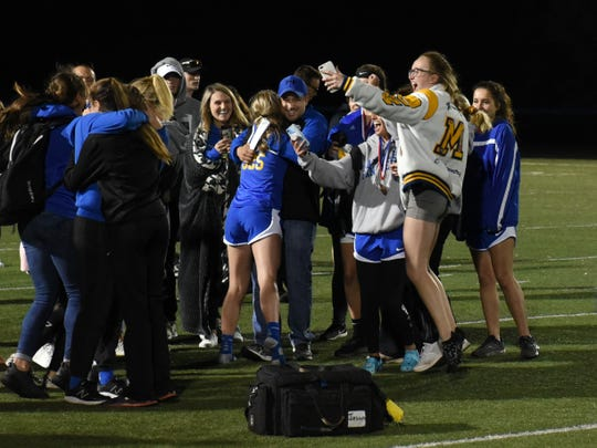 Maysville's girls team celebrates with coach Scott Gura after winning the Muskingum Valley League Track and Field Meet on Friday at Maysville. It was the Panthers' first league title in school history.