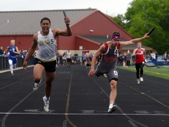 Tri-Valley's Jordan Pantaleo, left, and Sheridan's Jacob Rhodes lunge across the finish line in the 4x100 relay during the Muskingum Valley League Track and Field Meet on Friday at Maysville.