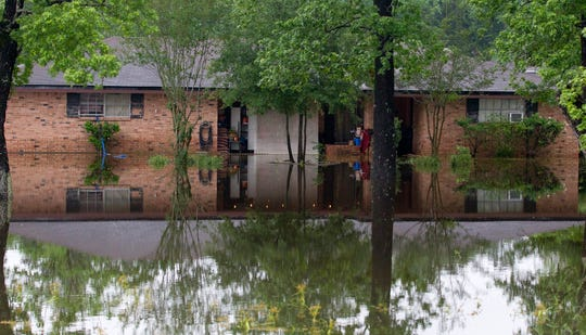 A home along FM 1314 is surrounded by water after thunderstorms, Friday, May 10, 2019, in Porter, Texas.