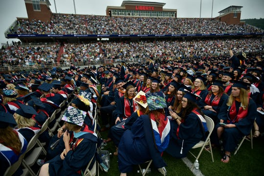 Graduates chat as students continue to walk in for Liberty University's Commencement ceremony in Lynchburg, Saturday, May 11, 2019. More than 45,000 people attended the event where Vice President Mike Pence delivered the commencement speech.