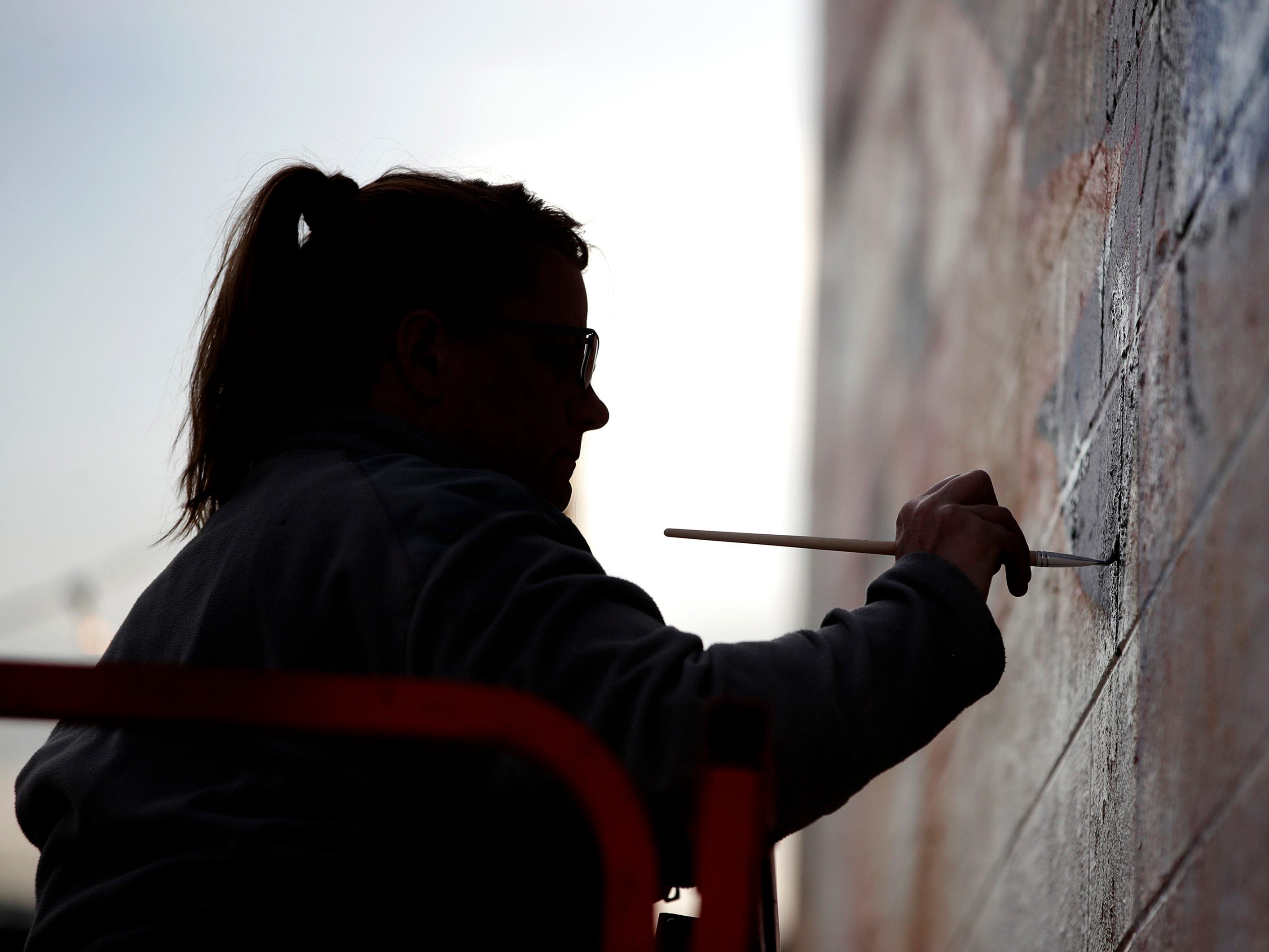 """Jodie Naze paints a mural entitled """"Brillion Pride"""" on the wall of Schroth Brillion Floral and Gifts during Bazaar After Dark Saturday, May 11, 2019, in Brillion, Wis. Danny Damiani/USA TODAY NETWORK-Wisconsin"""