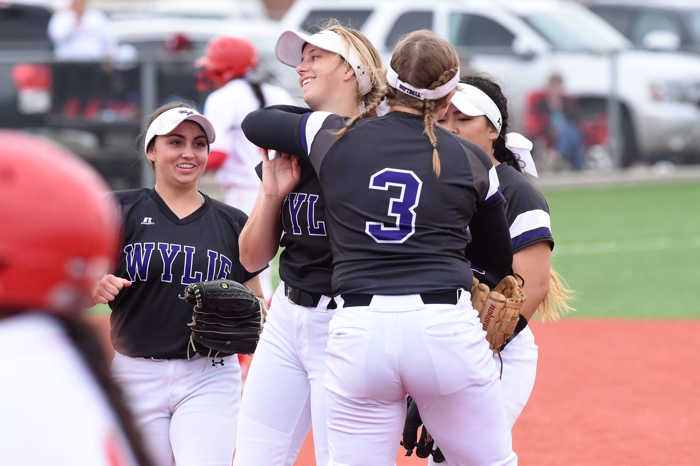 Wylie's Kaylee Philipp (3) hugs Kylie Barnes (13) after a double play against Lubbock Coronado in Game 3 of the Region I-5A quarterfinals. The Lady Bulldogs won a district title and reached the region semifinals in its first year competing in Class 5A.