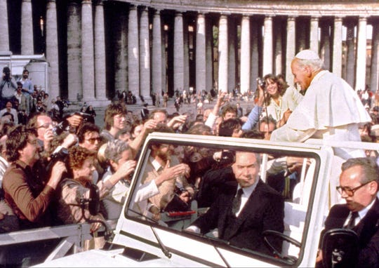 A hand holding a pistol, left, aims from the crowd at Pope John Paul II in St. Peter's Square in Rome on May 13, 1981.