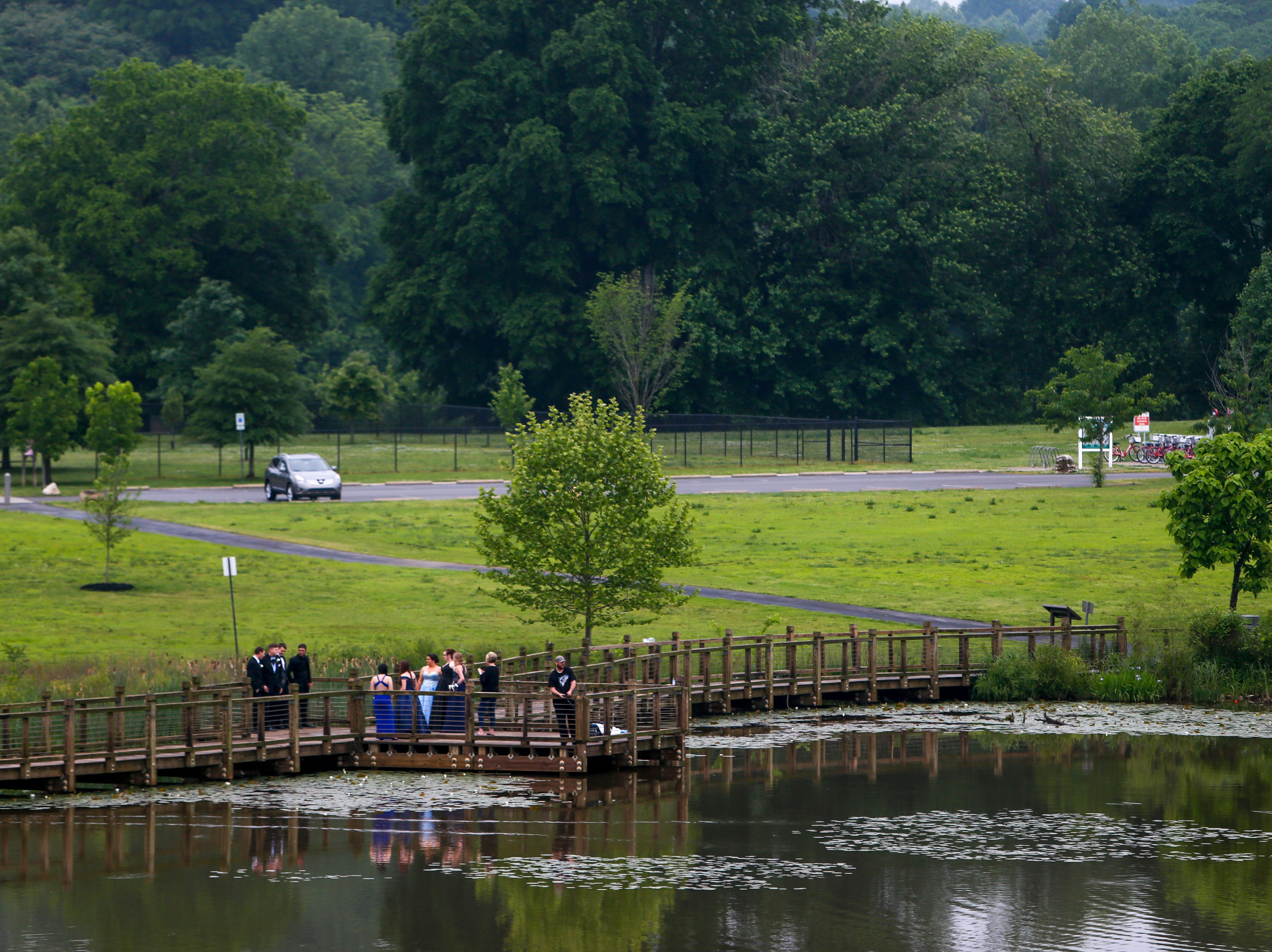 Prom attendees take photos on the docks around Liberty Park while fisherman continue to fish. Hundreds of seniors from Montgomery County Central High School celebrated their senior prom during a break from the weather in an otherwise rainy day at Wilma Rudolph Event Center in Clarksville, Tenn., on Saturday, May 11, 2019.