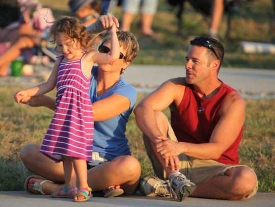 Janaya Williams, 2, of Des Moines dances with her grandmother, Gina Carlson, as Craig Murphy watches, during the Adjunct General's Summer Concert Series in 2012 at the historic Camp Dodge pool complex.