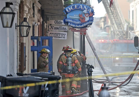 Firefighters exit the Oceana restaurant as the New Orleans Fire Department battles a fire in the French Quarter between Bourbon and Royal Streets in New Orleans.