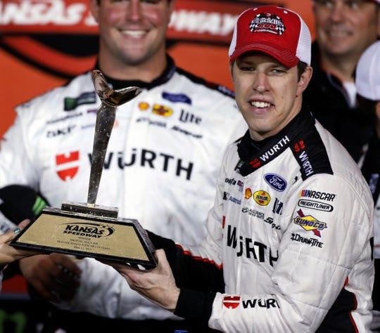 Brad Keselowski celebrates in Victory Lane after winning the NASCAR Cup Series auto race Saturday at Kansas Speedway in Kansas City, Kan.