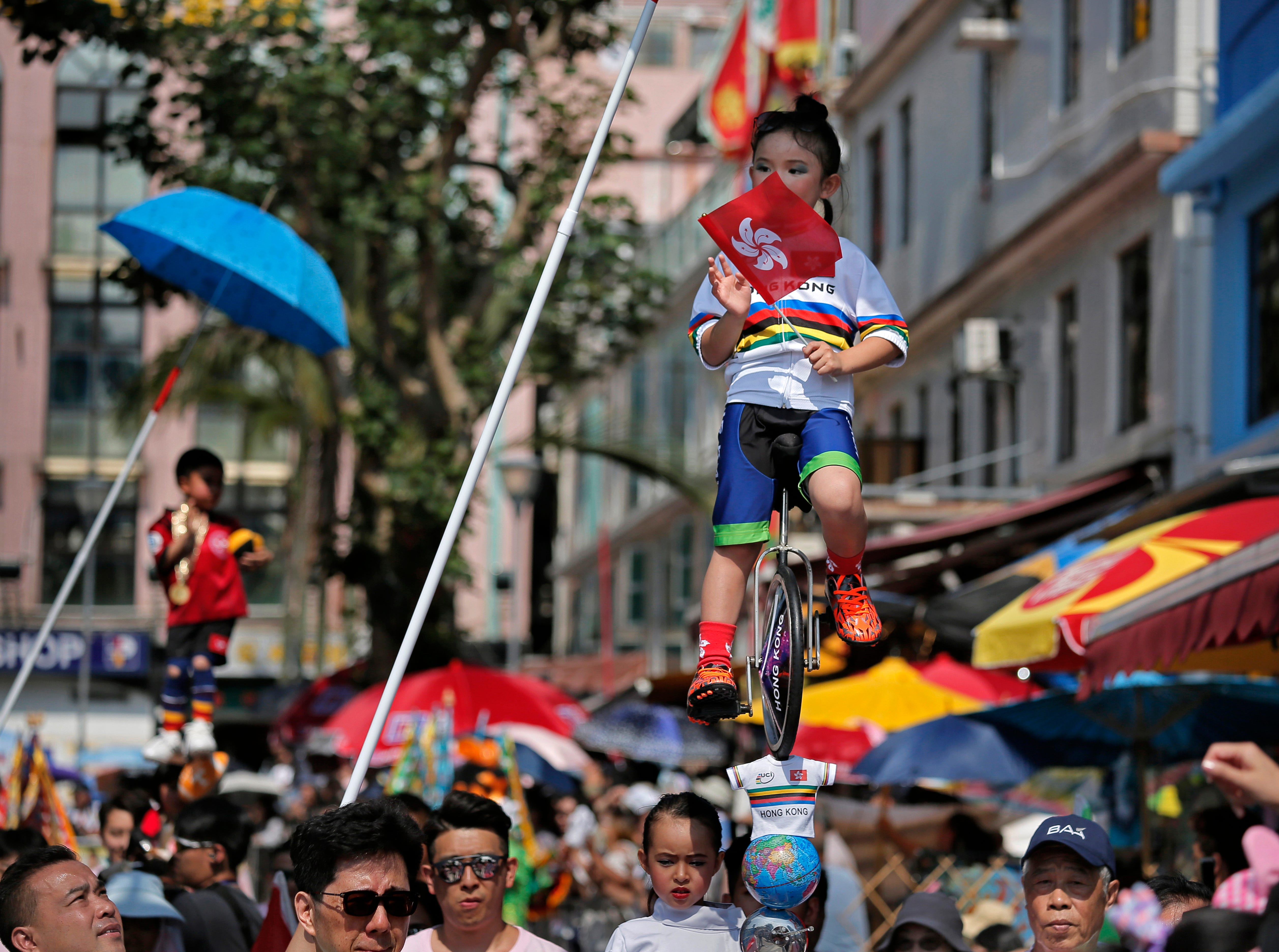 A child dressed in a traditional Chinese costume floats in the air, supported by a rig of hidden metal rods, during a parade on the outlying Cheung Chau island in Hong Kong to celebrate the Bun Festival Sunday, May 12, 2019.  Thousands of local residents and tourists flocked to an outlying island in Hong Kong to celebrate a local bun festival on Sunday. The festival features a parade with children dressed as deities floated on poles.