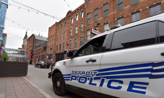 A Detroit police officer patrols Monroe Street near Beaubien in Greektown, Sunday morning. Police have made two arrests of the four suspects in the shooting.