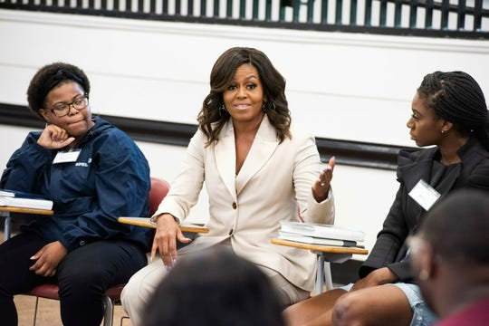 Michelle Obama, center, speaks with Rayven Peterson and Anta Njie of Morehouse College and Spelman College during a campus visit to Spelman College on Saturday, May 11, 2019, in Atlanta.