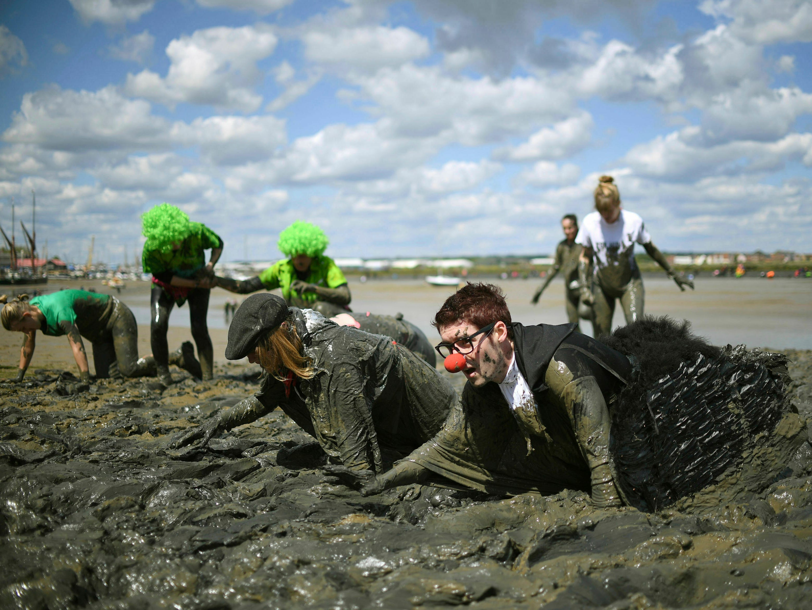 Competitors takes part in the annual Maldon Mud Race, a charity event to race across the bed of the River Blackwater in Maldon, southern England. Sunday May 12, 2019.