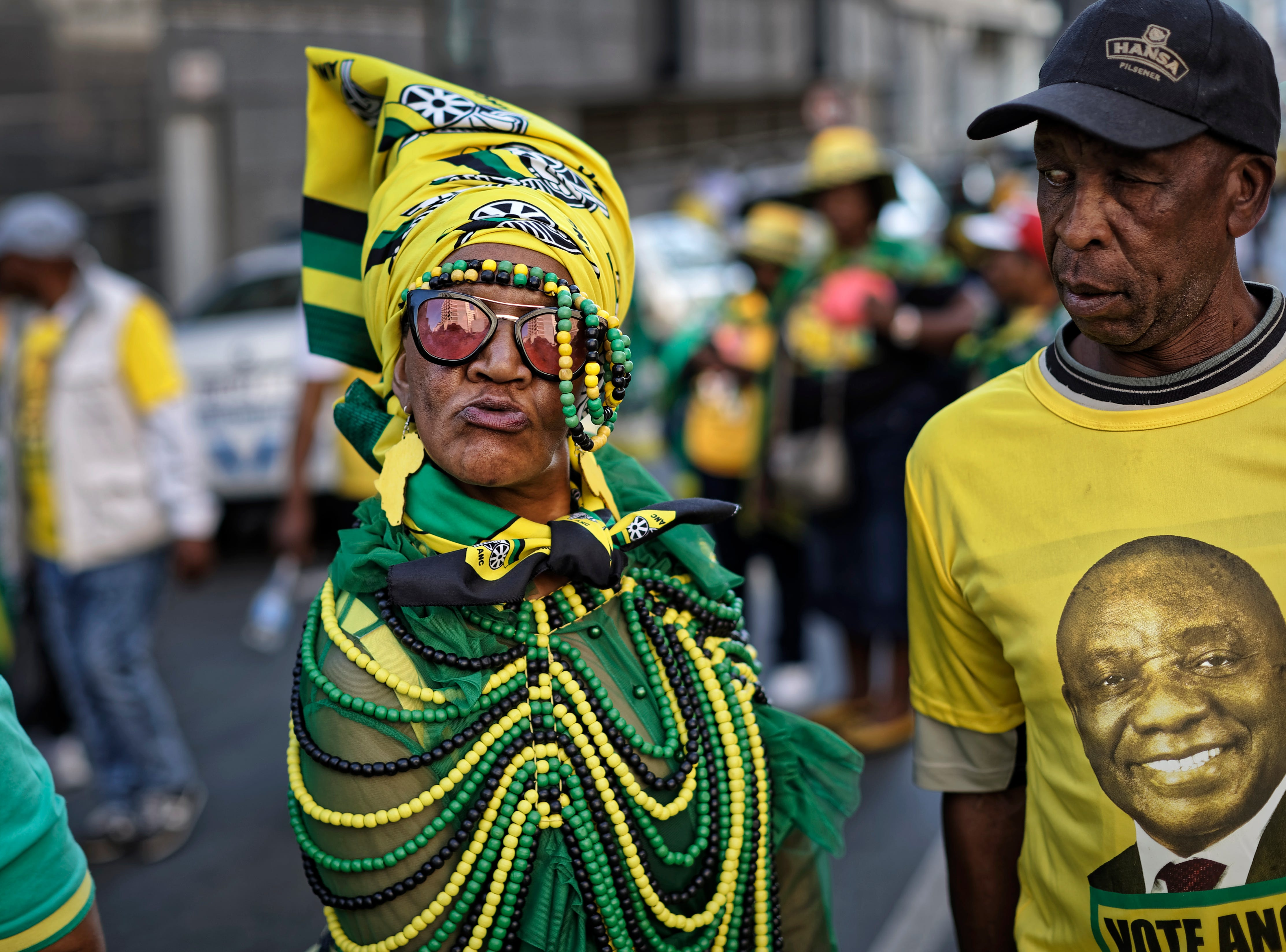 """A supporter of the African National Congress (ANC) party wears beads in the party colors, and another wears a t-shirt of President Cyril Ramaphosa, right, during a victory rally in downtown Johannesburg, South Africa Sunday, May 12, 2019. South Africa's president on Sunday vowed to purge his party of """"bad and deviant tendencies"""" as he prepares to appoint a new Cabinet following a victory in national elections."""